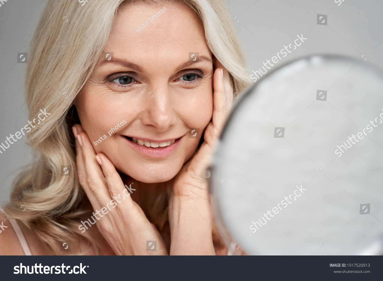 Happy 50s middle aged woman model touching face skin looking in mirror. Smiling mature older lady pampering, enjoying healthy skin care, aging beauty, skincare treatment cosmetic products concept. #1917520913
