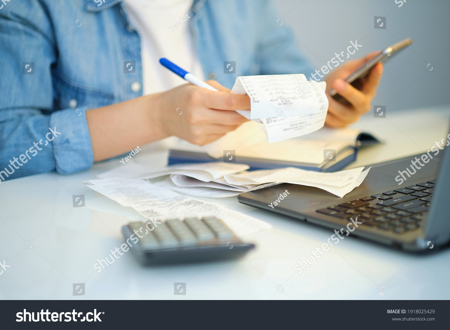 woman using a pen writing on bank account book while holding the bills to calculate in living room at home. Expenses, account, taxes, home budget concept #1918025429