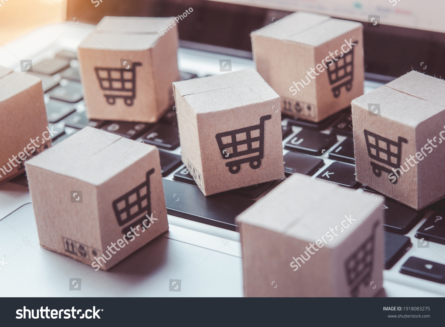 Shopping online. Cardboard box with a shopping cart logo on laptop keyboard. Shopping service on The online web. offers home delivery #1918083275