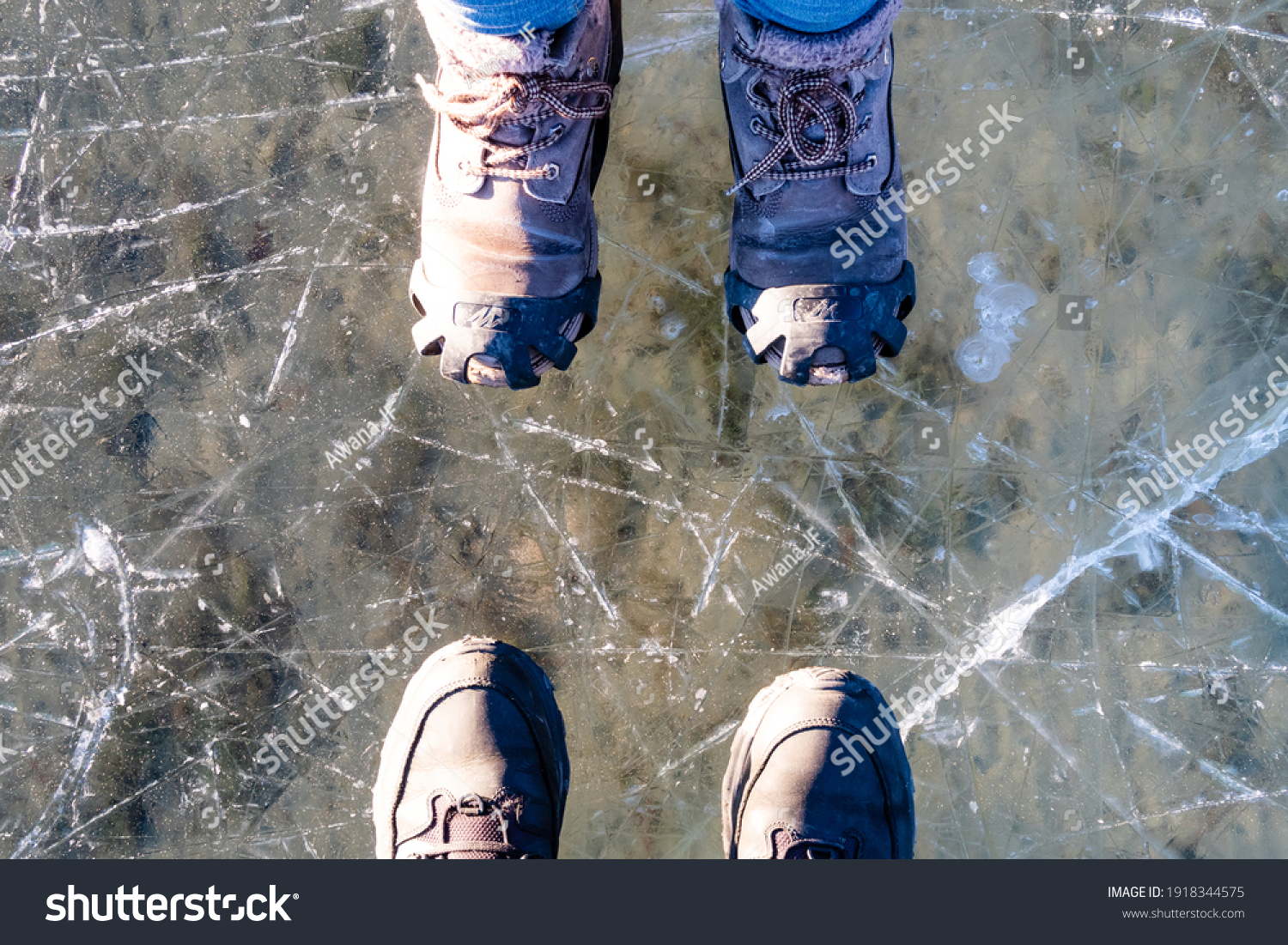 Banff national park, Canada - december  2020 : Top view of two pairs of winter boots on a frozen lake in Canada