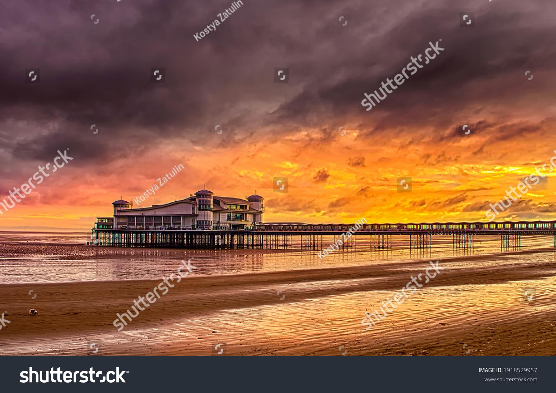 Sunset sea pier on the beach. Sunset beach pier. Sunset beach pier view. Sunset sea beach pier panorama #1918529957