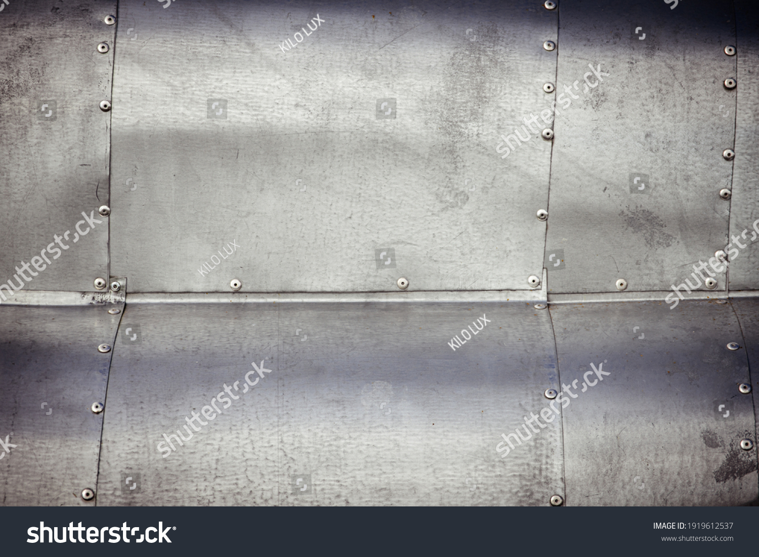 Riveted, sheet metal, waved, weathered surface abstract background image. #1919612537