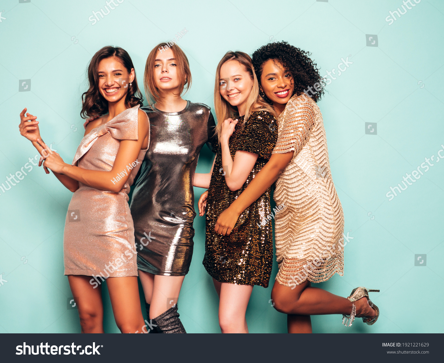 Four young international beautiful brunette women in trendy summer  shiny dress.Sexy smiling carefree female posing near blue wall in studio.Fashionable models with bright evening makeup #1921221629