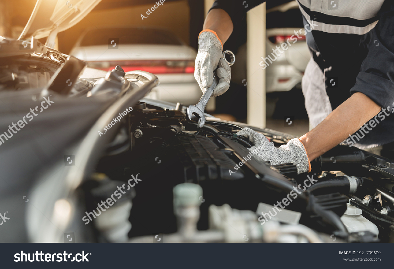 Automobile mechanic repairman hands repairing a car engine automotive workshop with a wrench, car service and maintenance,Repair service. #1921799609