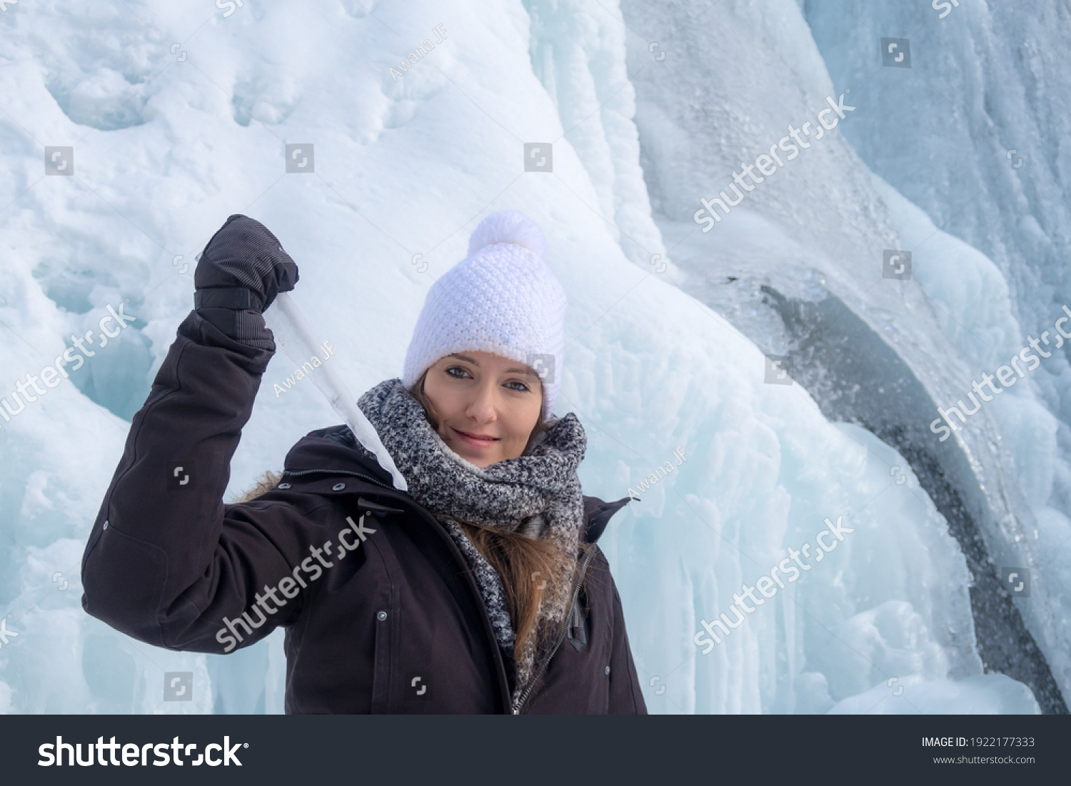 Young woman holding a sharp icicle in front of the Tangle Creek Falls, in Alberta, Canada