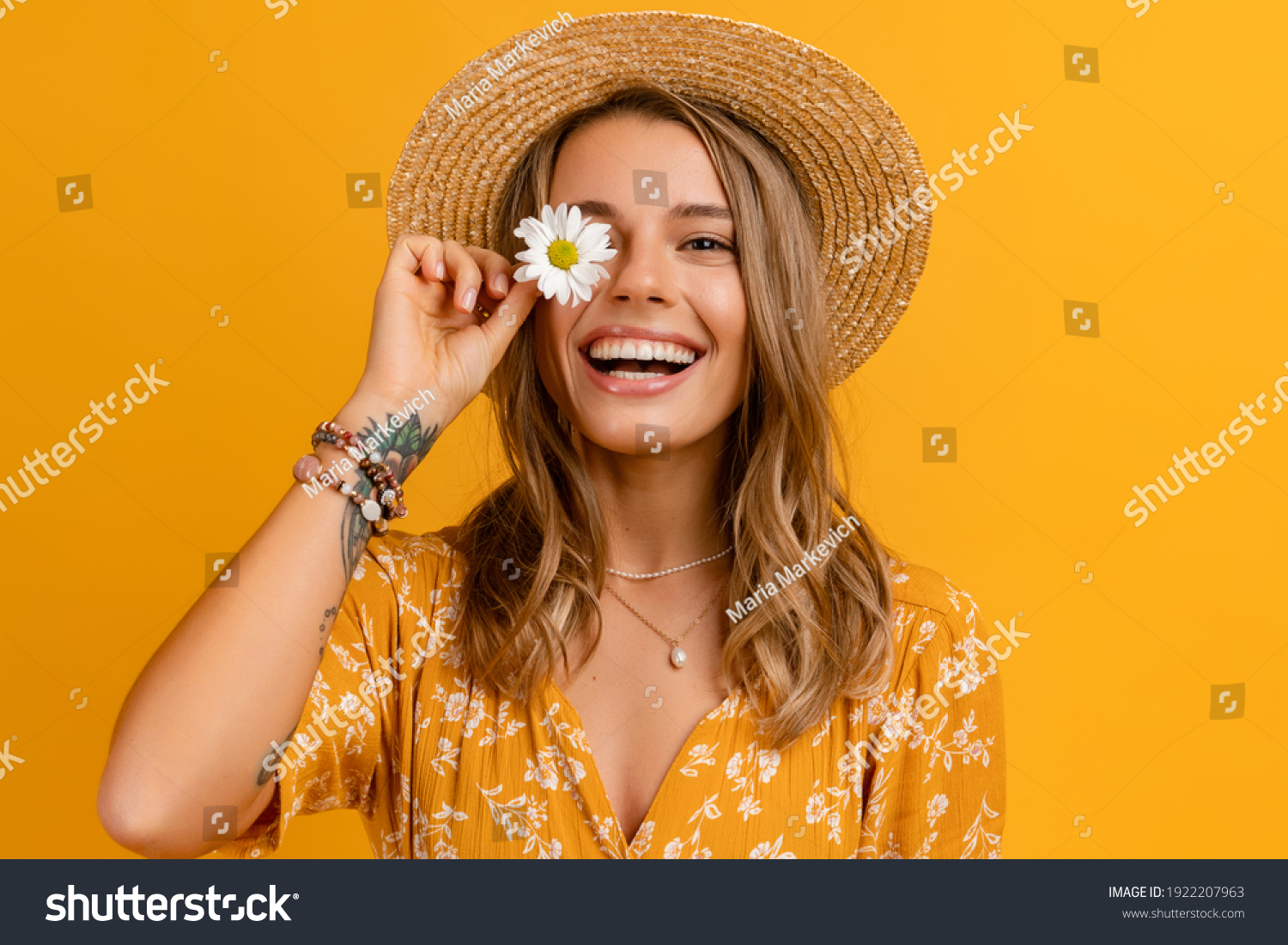 beautiful attractive stylish woman in yellow dress and straw hat holding daisy flower romantic mood posing on yellow background isolated in love summer fashion trend style, natural look #1922207963