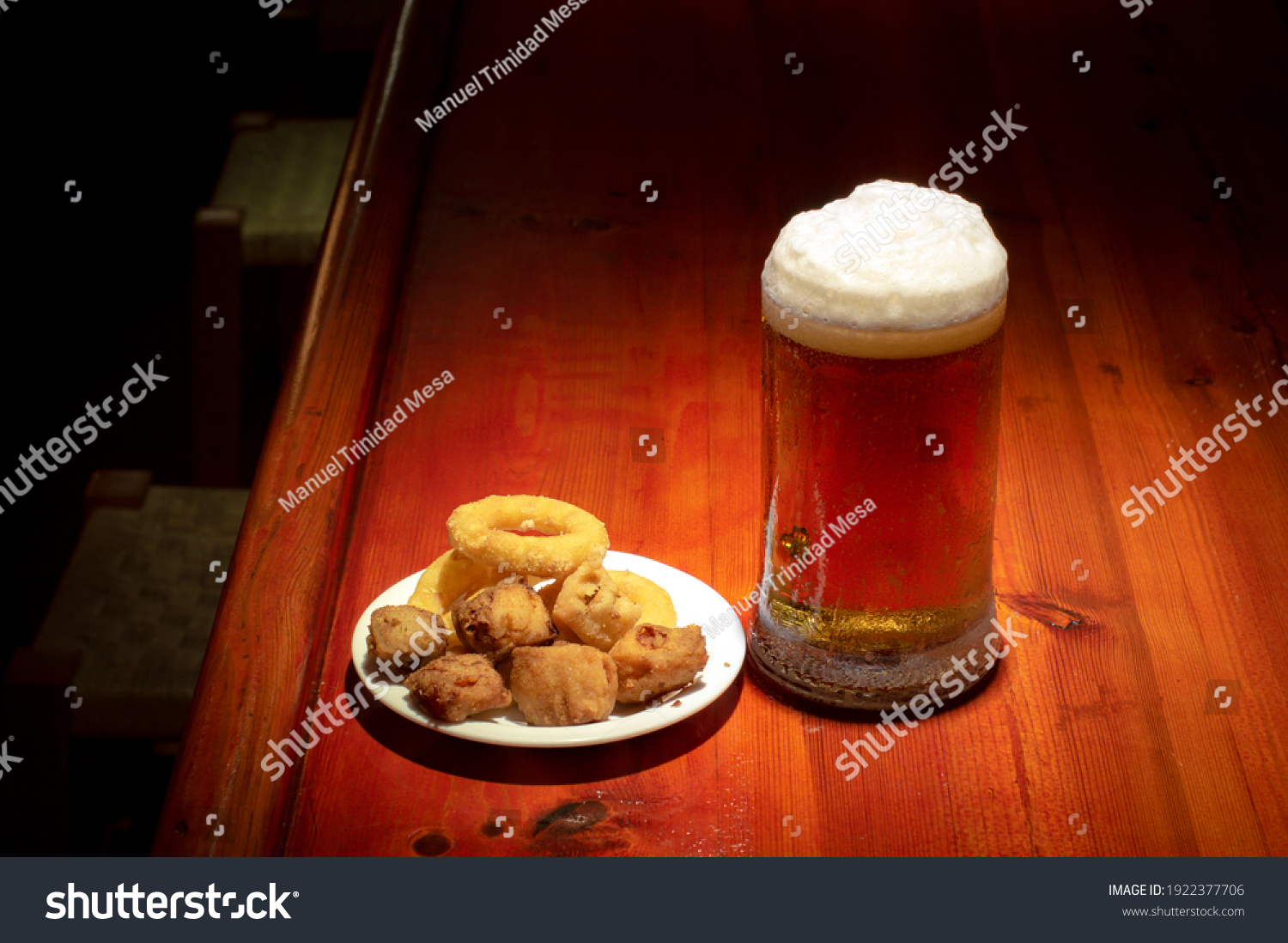 Assorted fried fish and a cold beer on a bar counter