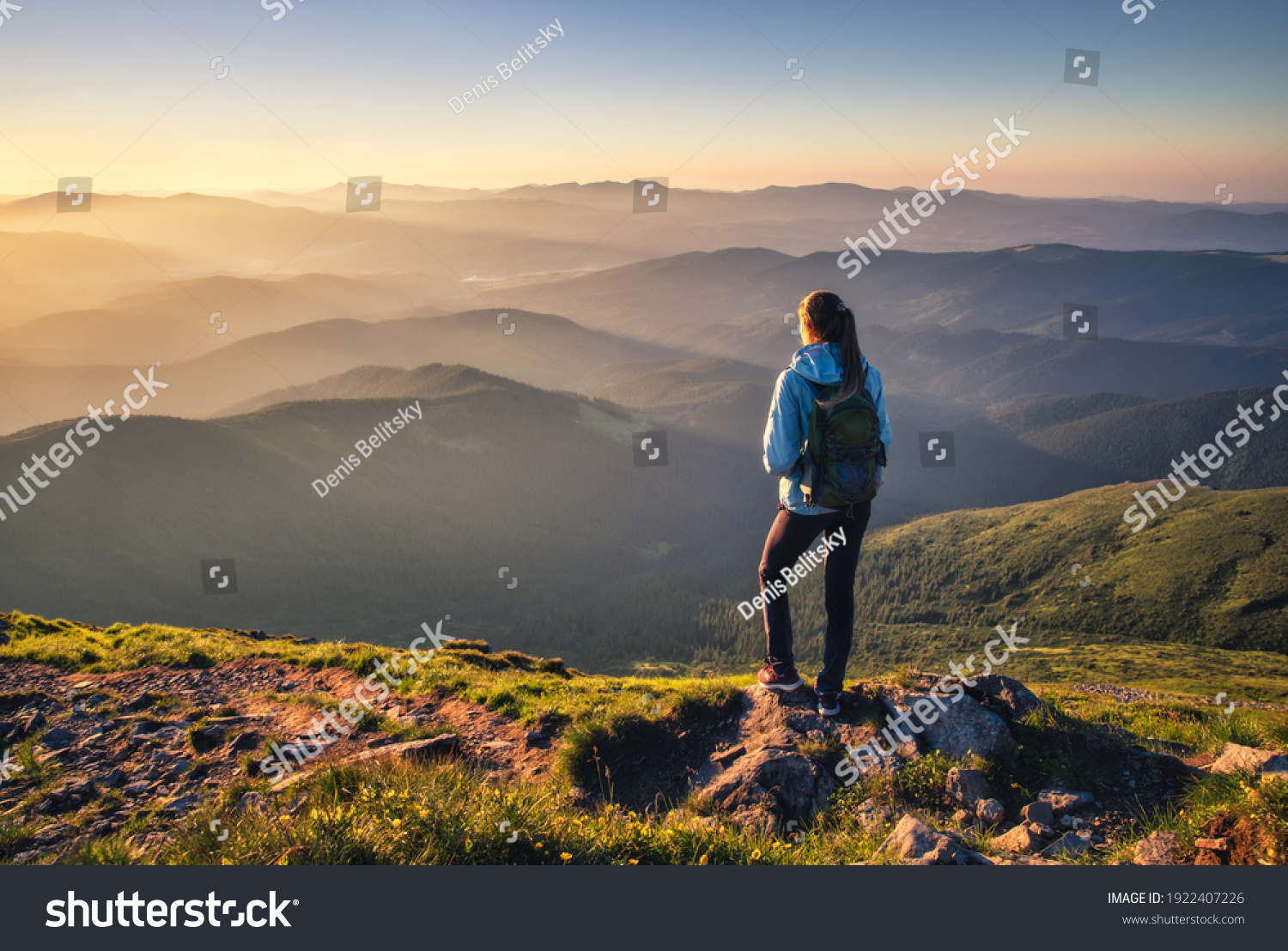 Girl on mountain peak with green grass looking at beautiful mountain valley in fog at sunset in summer. Landscape with sporty young woman, foggy hills, forest, sky. Travel and tourism. Hiking #1922407226