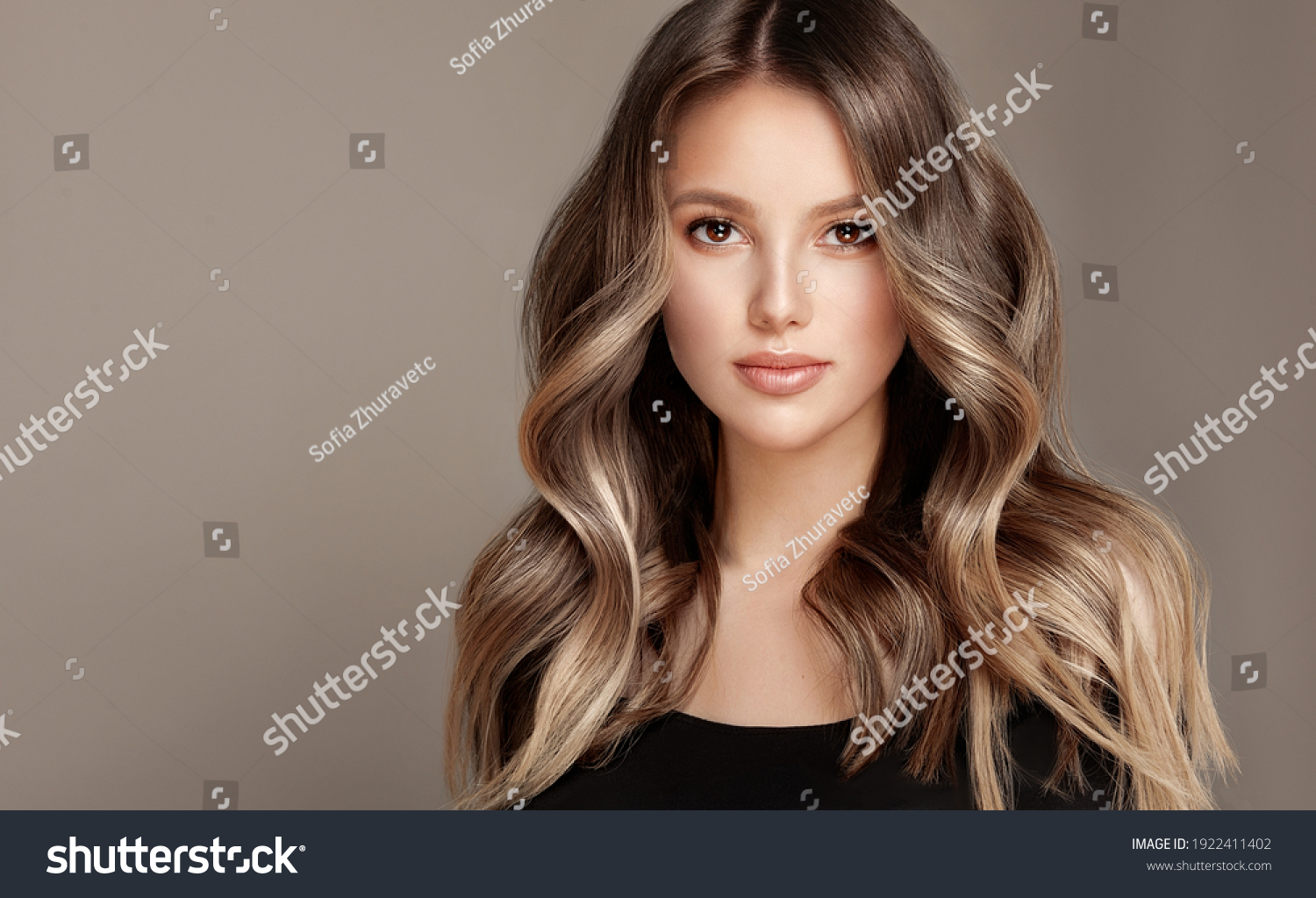 Beauty  girl with long  and   shiny wavy  Hair ,coloring and toning, shatush and balayash .  Beautiful   woman model with curly hairstyle . #1922411402