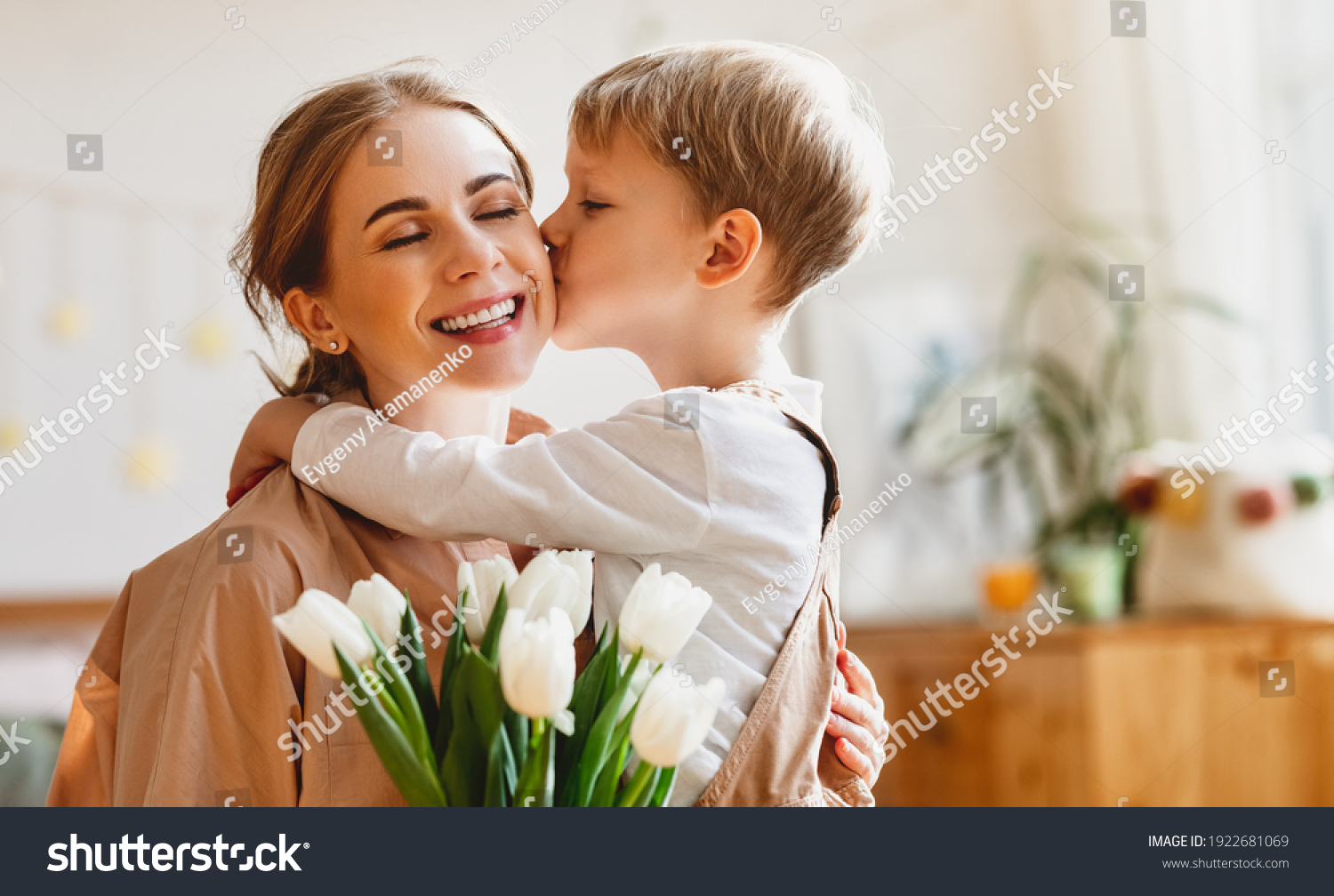 tender son kisses the happy mother and gives her a bouquet of tulips, congratulating her on mother's day during holiday celebration at home #1922681069