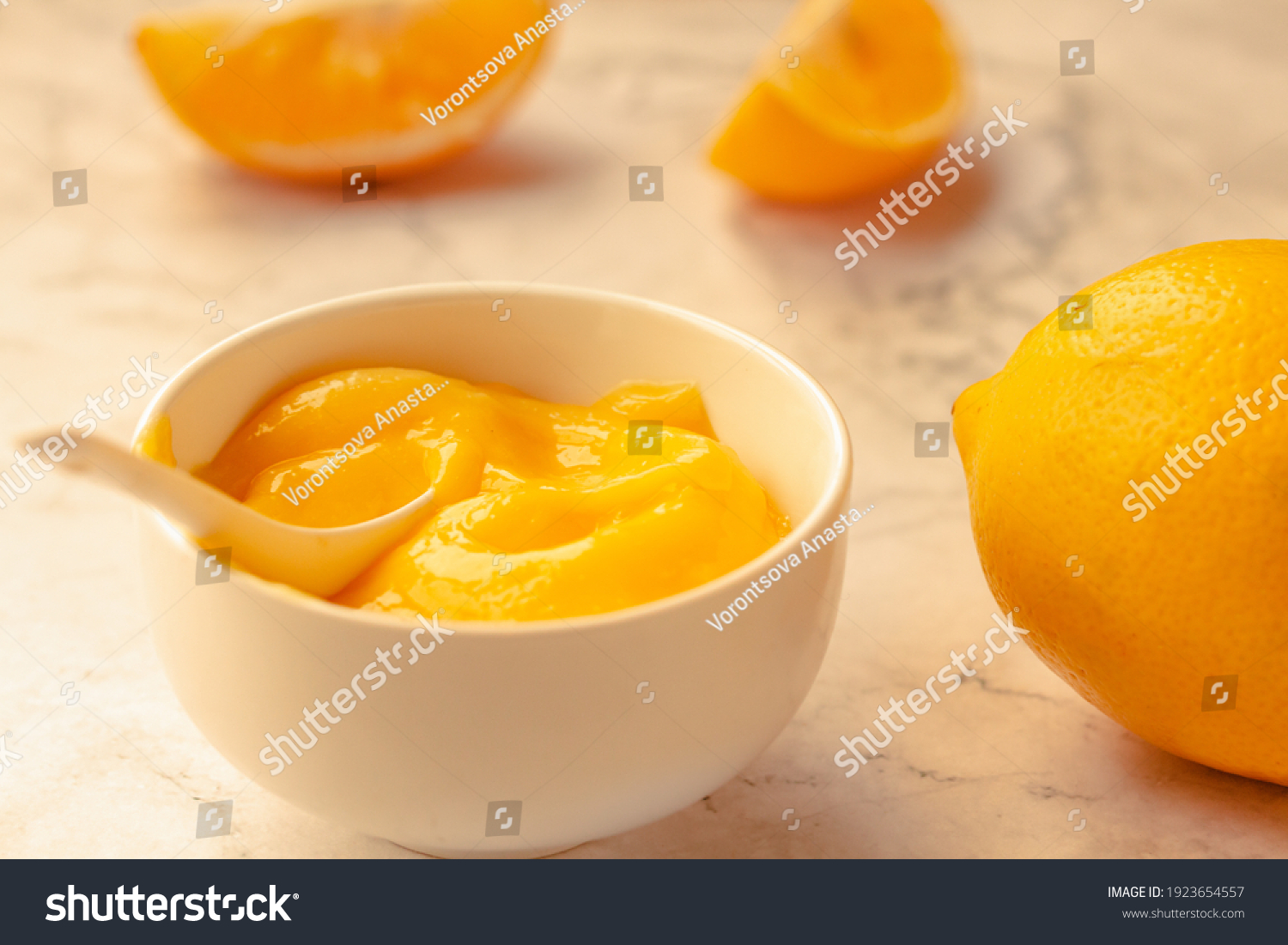 Composition with delicious Yellow lemons and Lemon curd in a sausepan white bowl on marble background. #1923654557