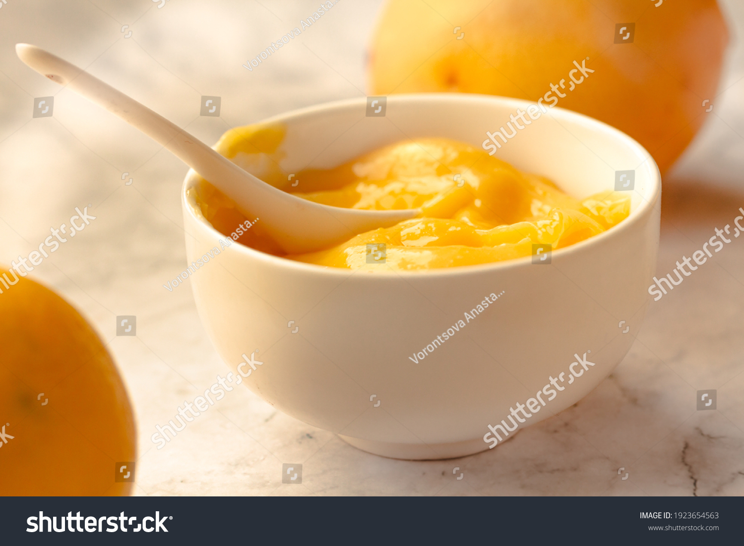 Composition with delicious Yellow lemons and Lemon curd in a sausepan white bowl on marble background. #1923654563