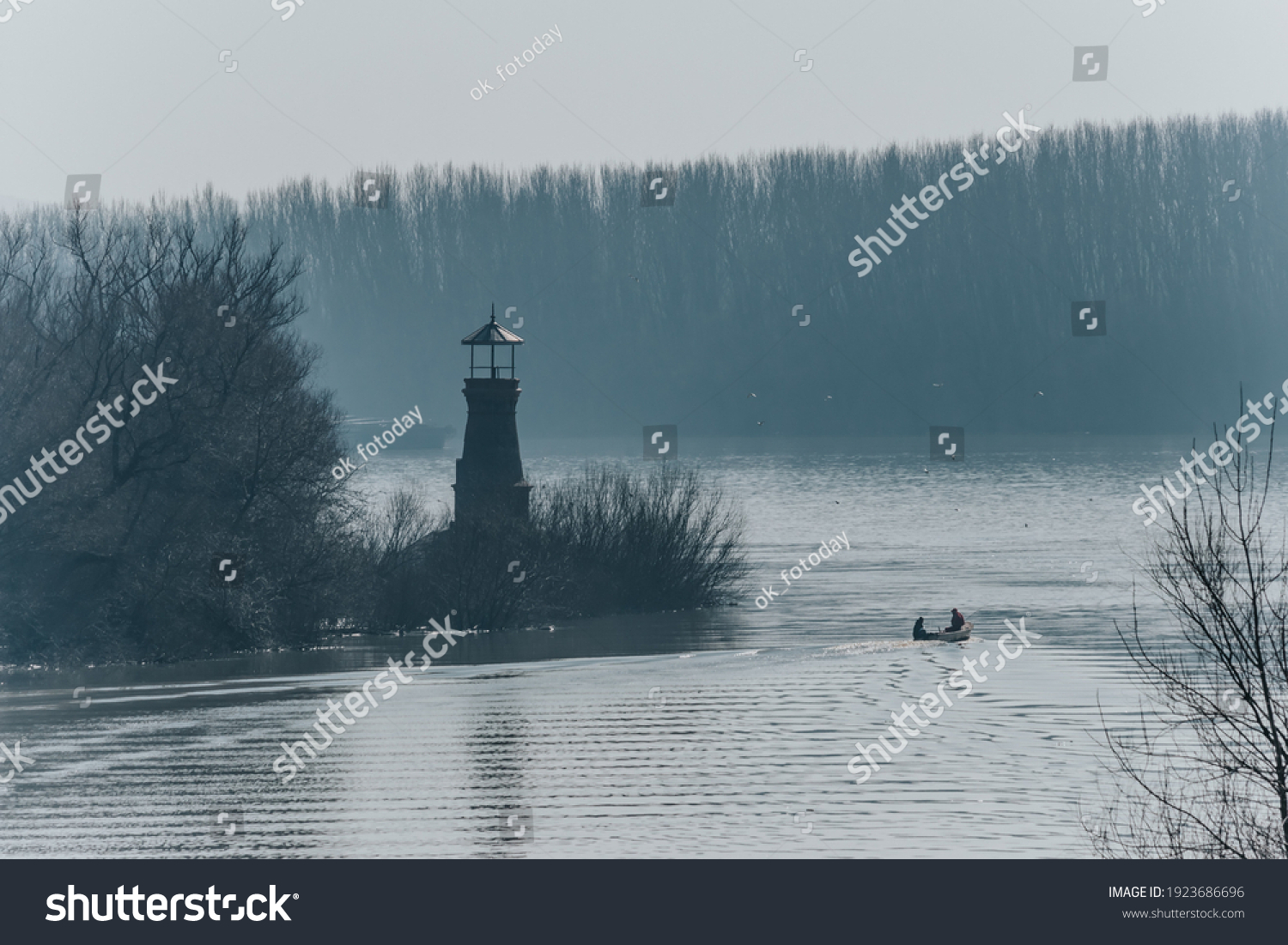 Beautiful mystical landscape on the river, in the distance a lighthouse and a small boat with people in backlight and a slight haze over the water