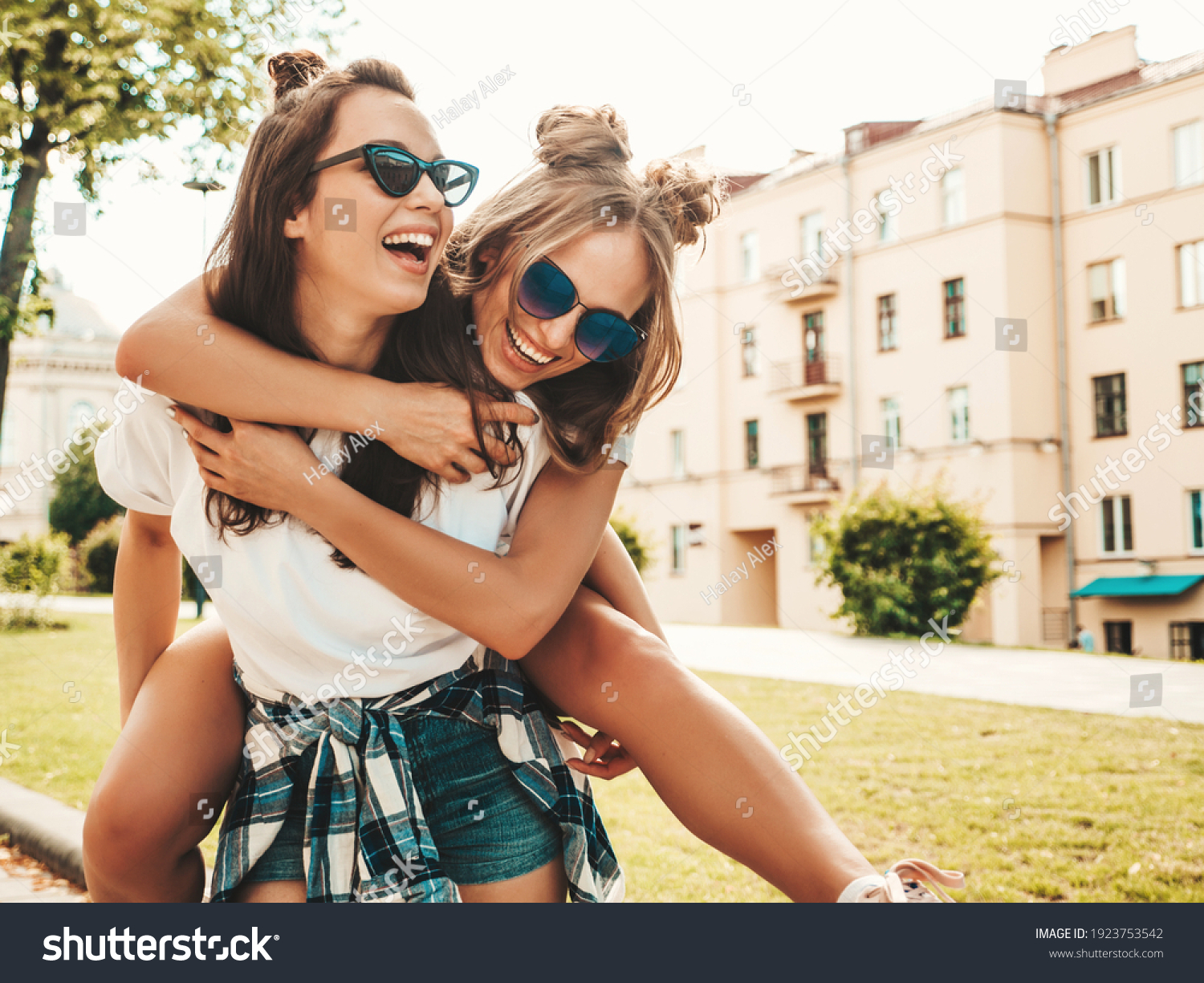 Two young beautiful smiling hipster female in trendy summer white t-shirt clothes.Sexy carefree women posing on street background. Model jumping on her friend back, gives piggyback riding outdoors #1923753542