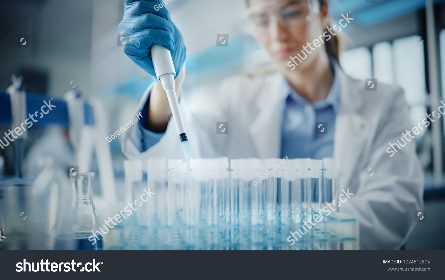 Medical Research Laboratory: Portrait of a Beautiful Female Scientist in Goggles Using Micro Pipette for Test Analysis. Advanced Scientific Lab for Medicine, Biotechnology, Microbiology Development #1924512605
