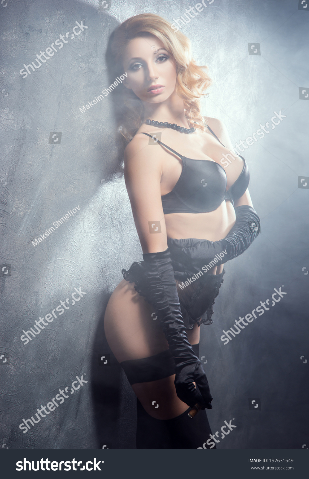 50c14c508 Young and beautiful cabaret dancer in sexy vintage lingerie smoking cigar  over retro background