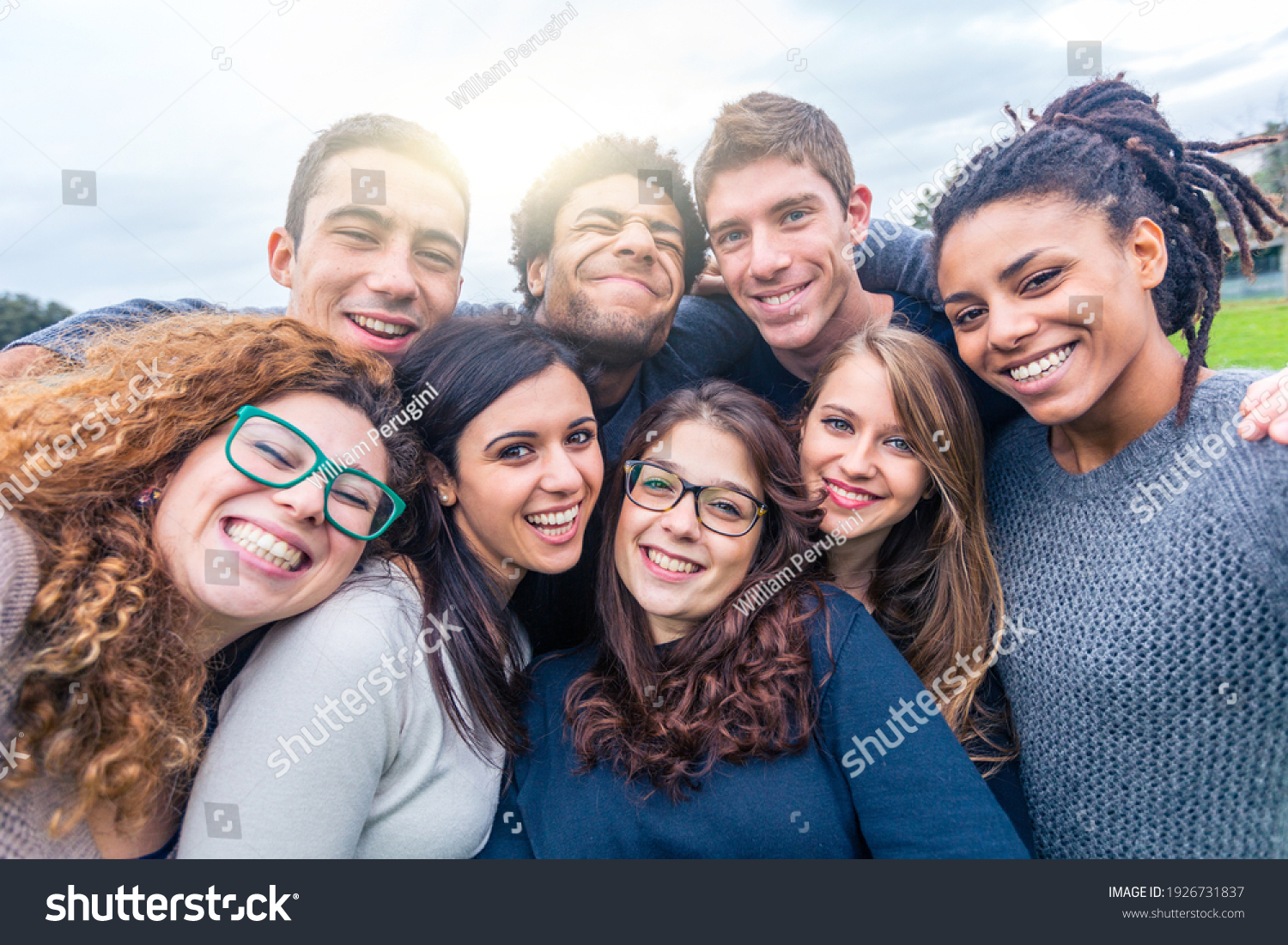Multiracial people together in a selfie making funny faces - Group of friends with mixed races having fun together at park - Friendship and lifestyle concepts #1926731837