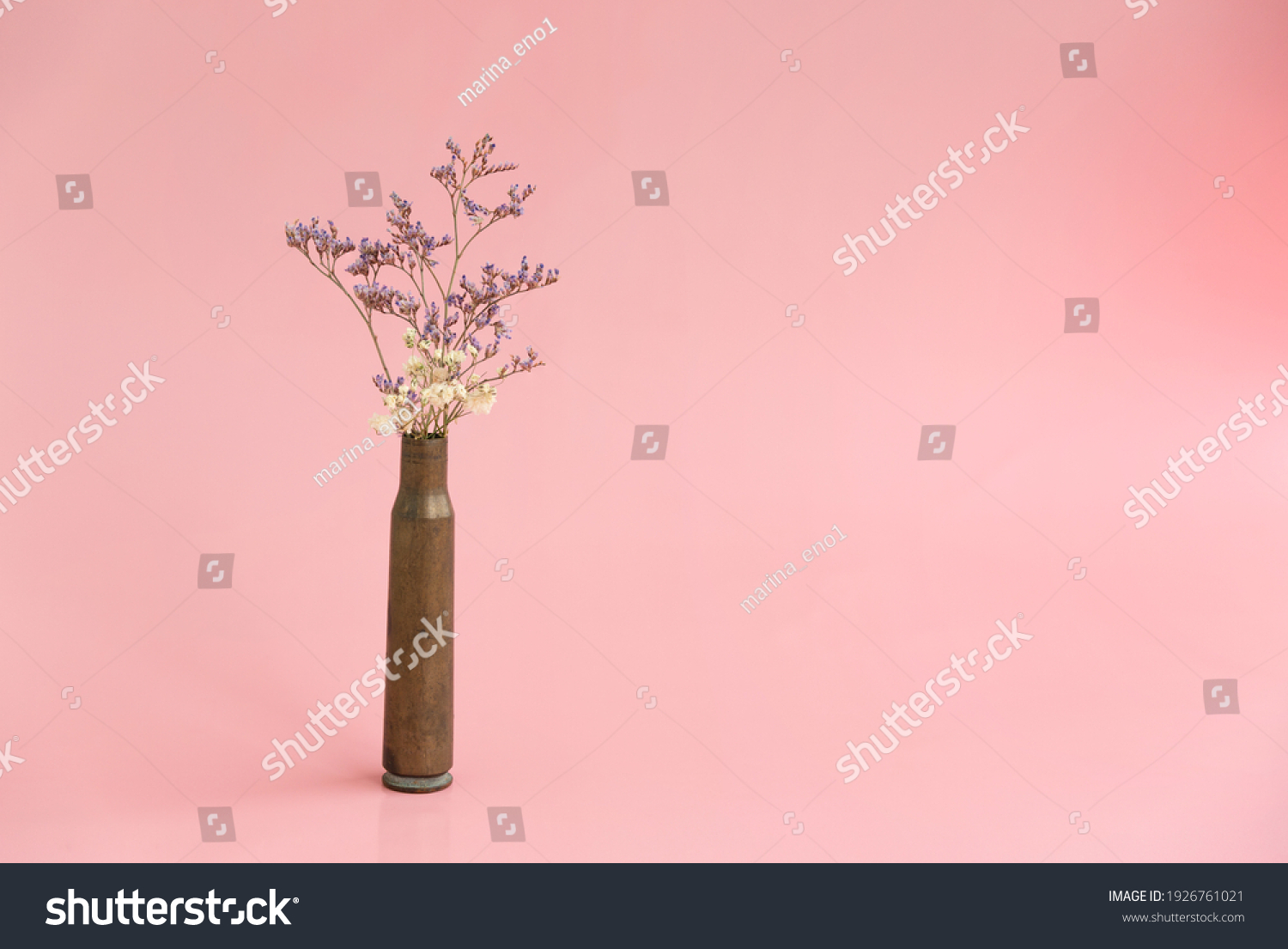 Dried flowers in an empty case from under a firearm on a pink background #1926761021