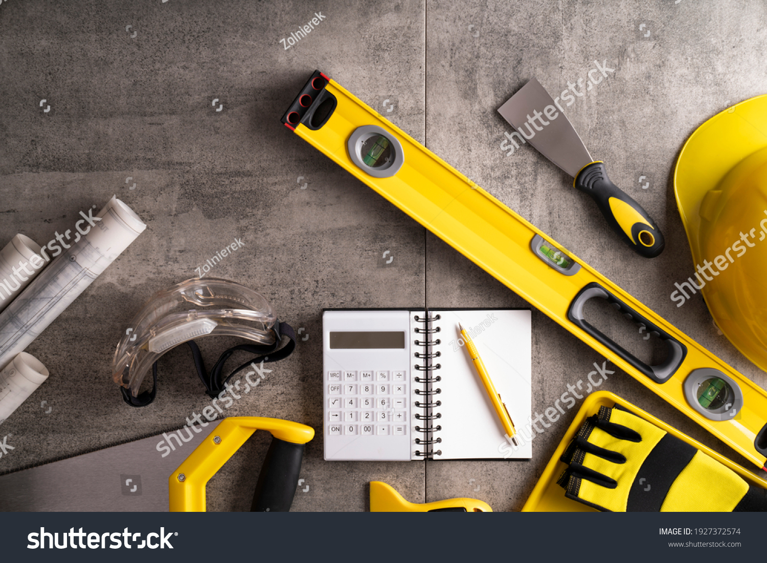 Yellow and black contractor equipment on gray tiles. #1927372574