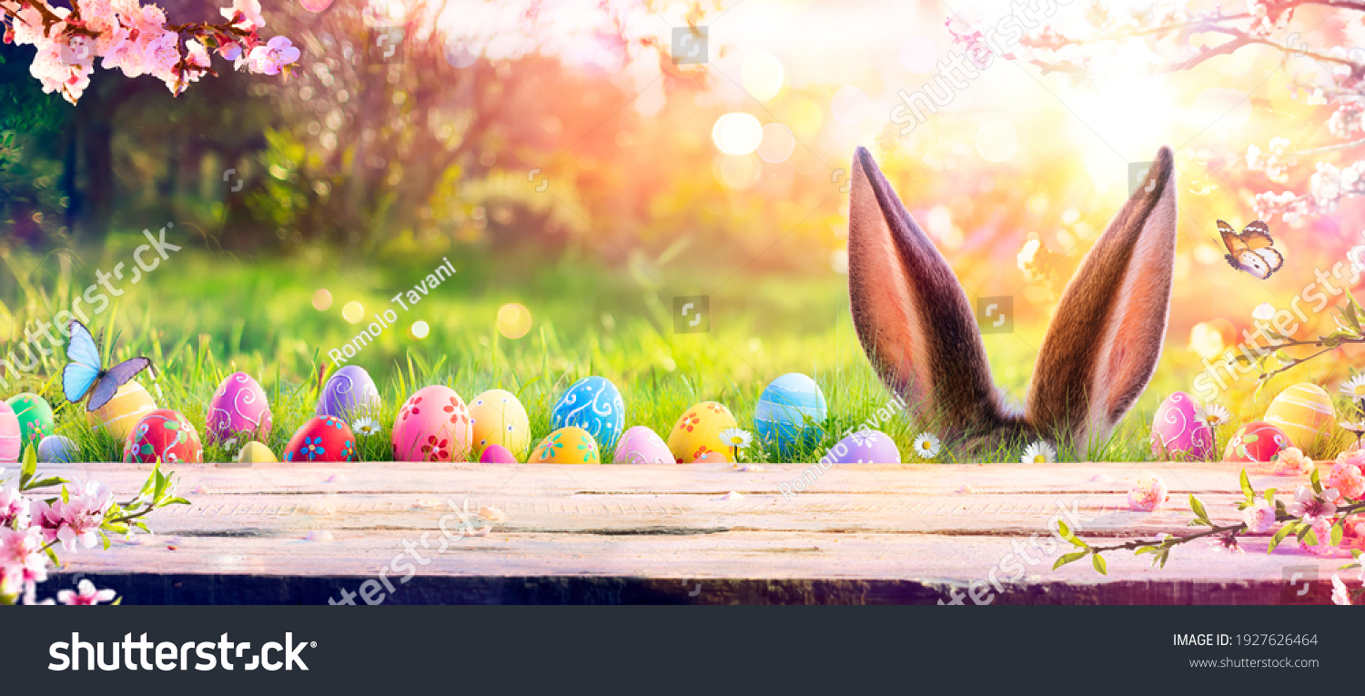 Abstract Defocused Easter Scene - Ears Bunny Behind Grass And Decorated Eggs In Flowery Field #1927626464