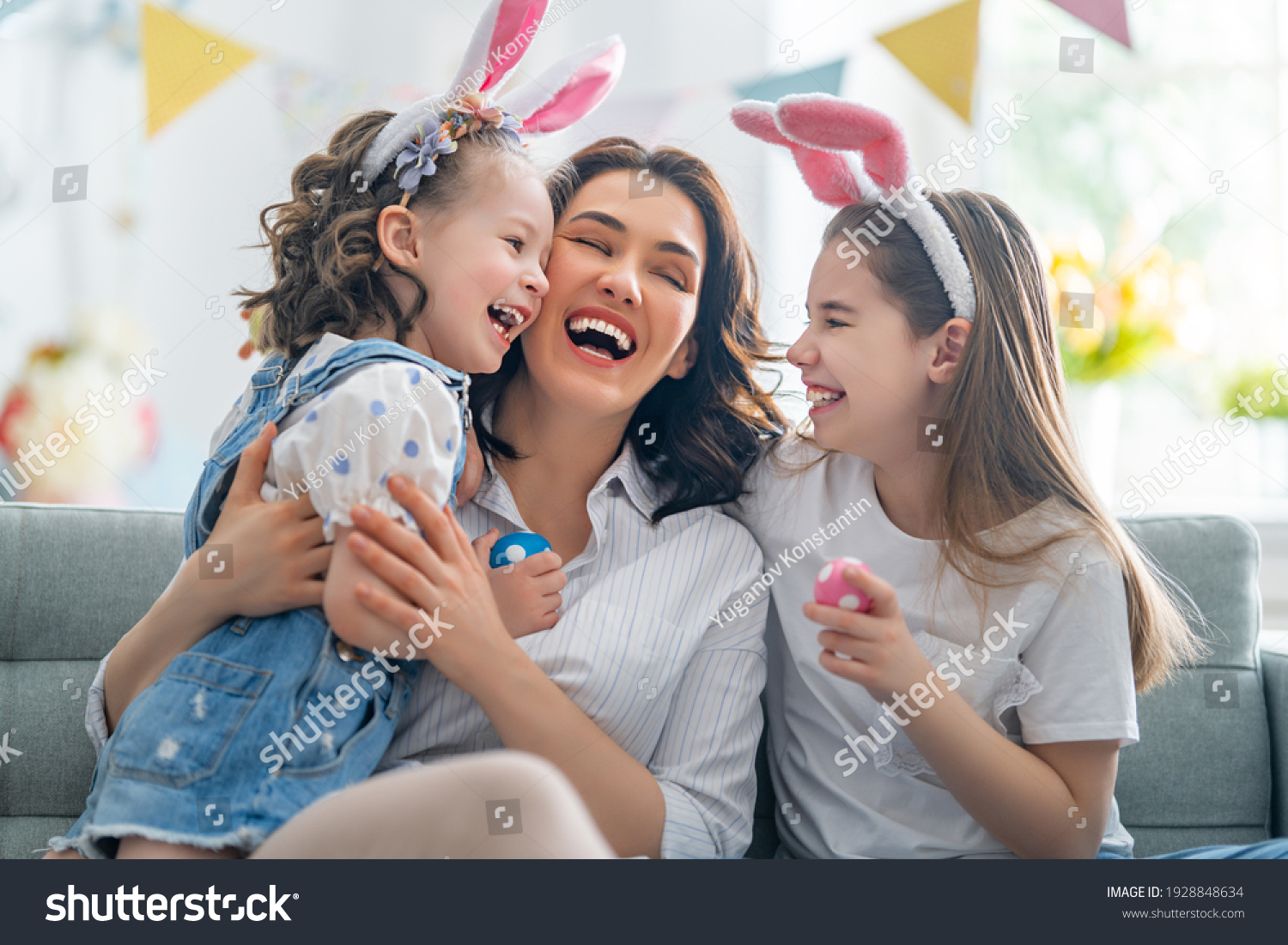 Happy holiday! Mother and her daughters with painting eggs. Family celebrating Easter. Cute little children girls are wearing bunny ears.  #1928848634