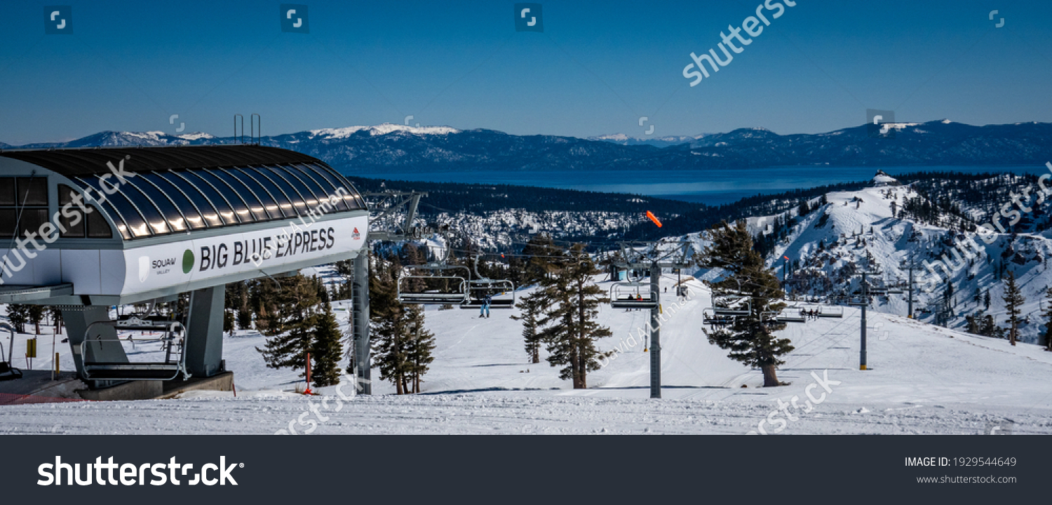 Olympic Valley, California - February 24,2021: The Big Blue Express chairlift carries skiers and snowboarders to the top of the Squa Valley Ski Resort, with view of lake tahoe in the background.