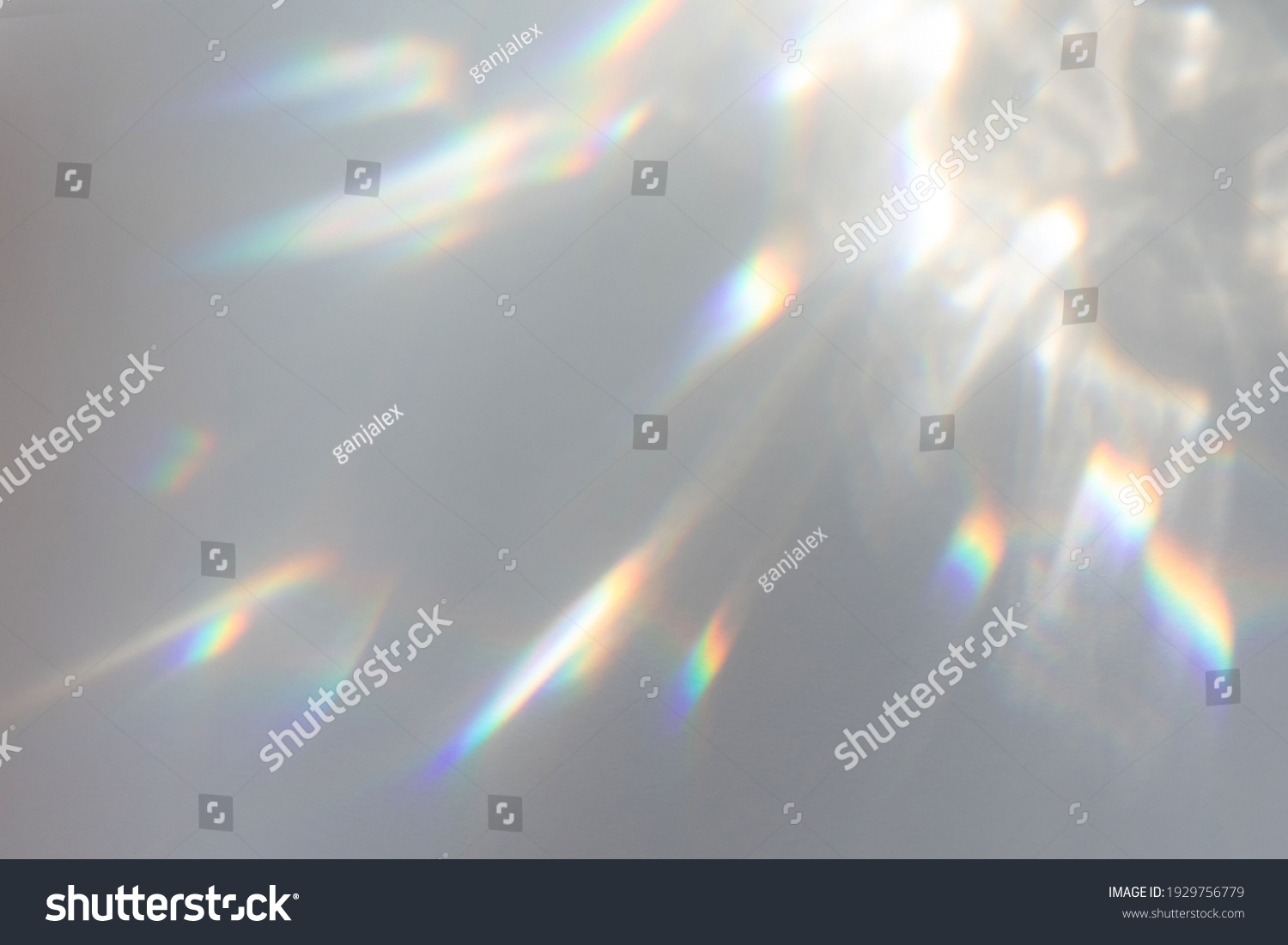 Blurred rainbow light refraction texture overlay effect for photo and mockups. Organic drop diagonal holographic flare on a white wall. Shadows for natural light effects #1929756779