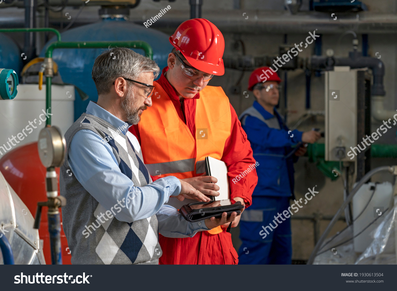 Technical Manager Using Digital Tablet and Discussing About Production Process with Power Plant Worker. District Heating Power Plant. Digital Technology and Teamwork Concept. Industry 4.0  #1930613504