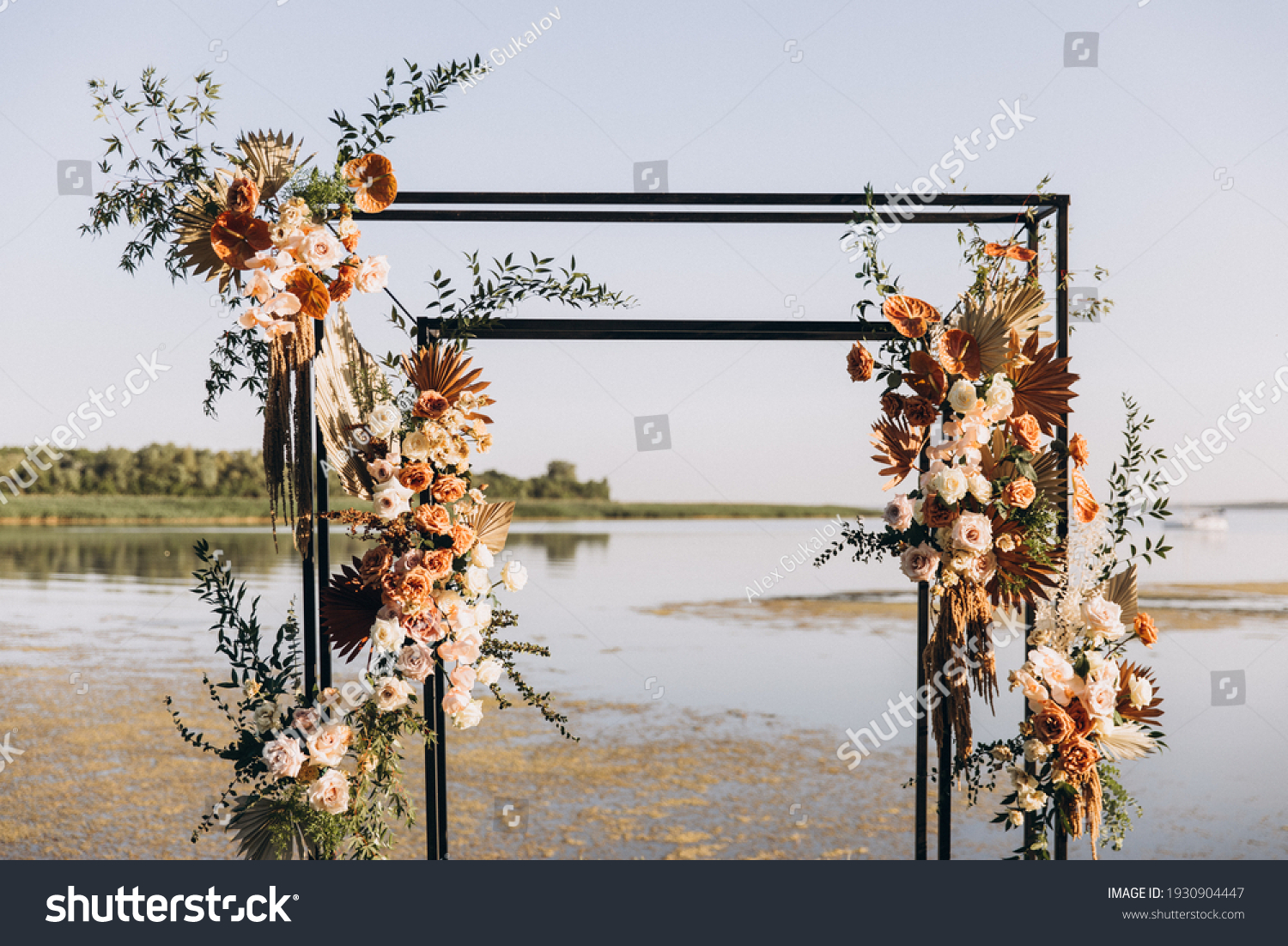 Wedding ceremony. On a green meadow on the seashore there is an arch decorated with flower arrangements, chairs for guests, candles and lamps #1930904447