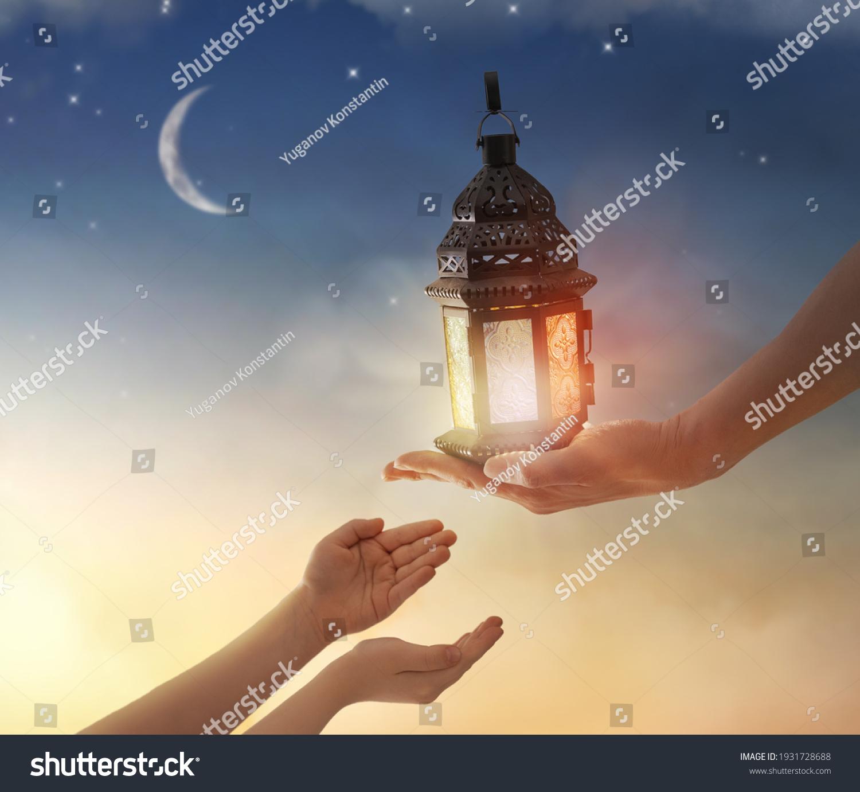 Ornamental Arabic lantern with burning candle glowing in hand. Festive greeting card, invitation for Muslim holy month Ramadan Kareem. #1931728688