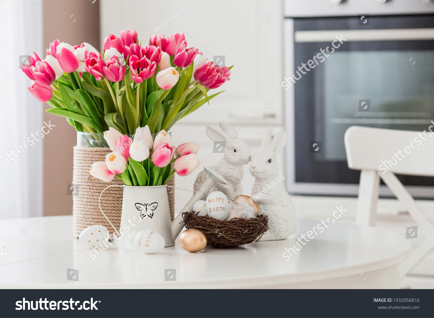 A bouquet of tulips, Easter bunnies and eggs with a golden pattern on the table. In the background is a white Scandinavian-style kitchen. Beautiful greeting card. The minimal concept. #1932056816