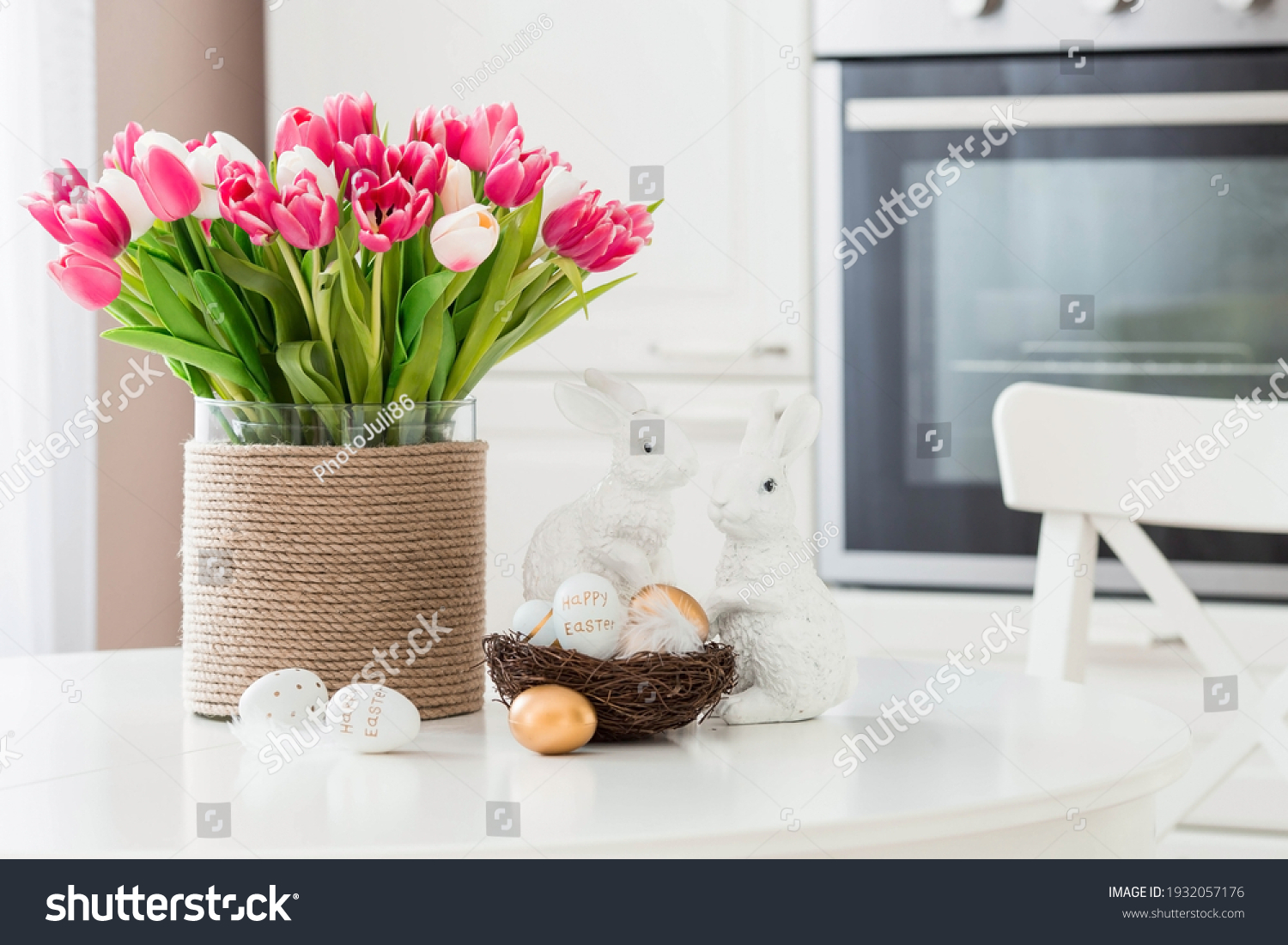 A bouquet of tulips, Easter bunnies and eggs with a golden pattern on the table. In the background is a white Scandinavian-style kitchen. Beautiful greeting card. The minimal concept. #1932057176
