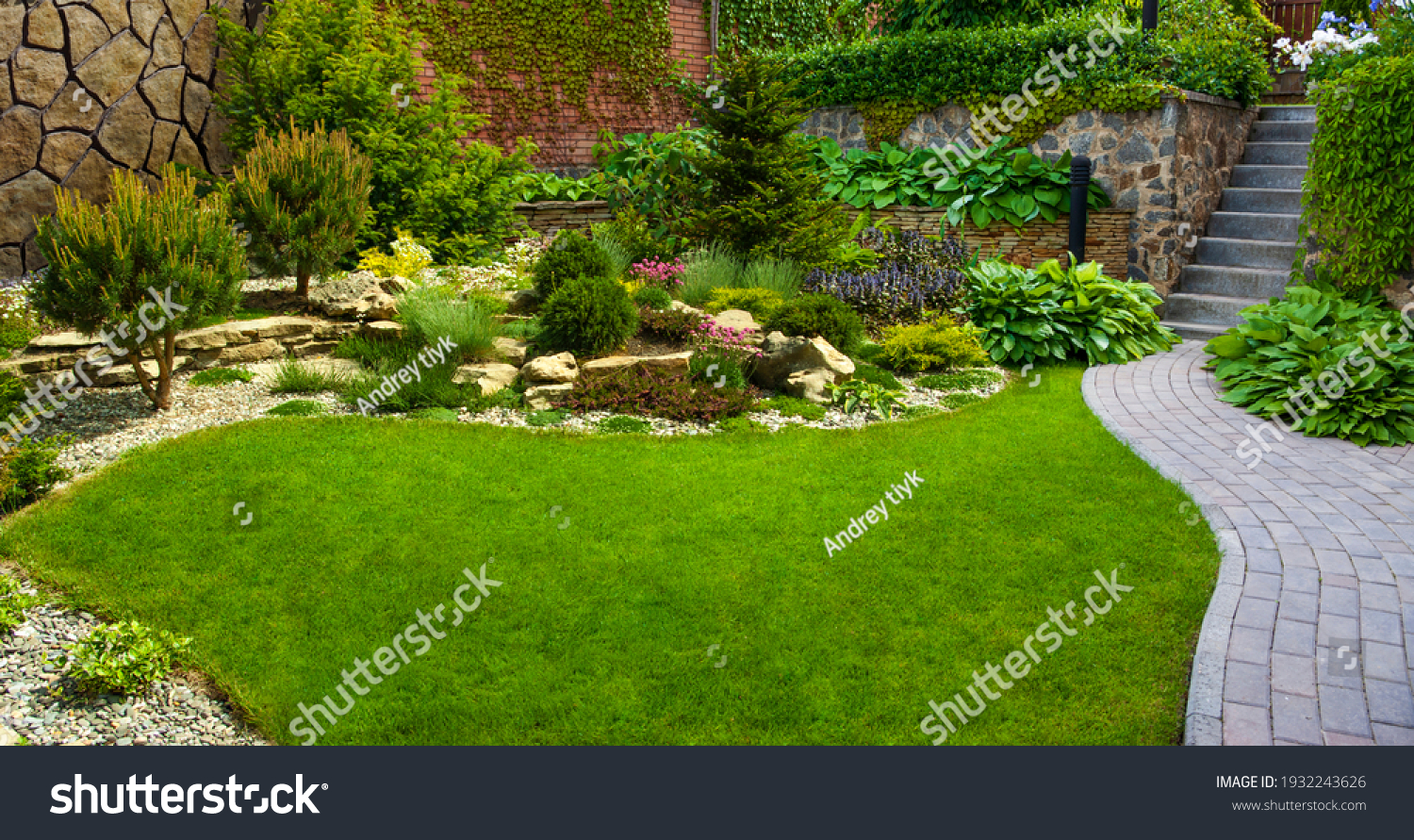 Garden stone path with grass growing up between the stones.Detail of a botanical garden. #1932243626