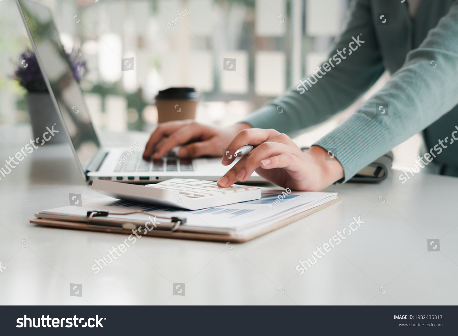 businessman working on desk office with using a calculator to calculate the numbers, finance accounting concept #1932435317