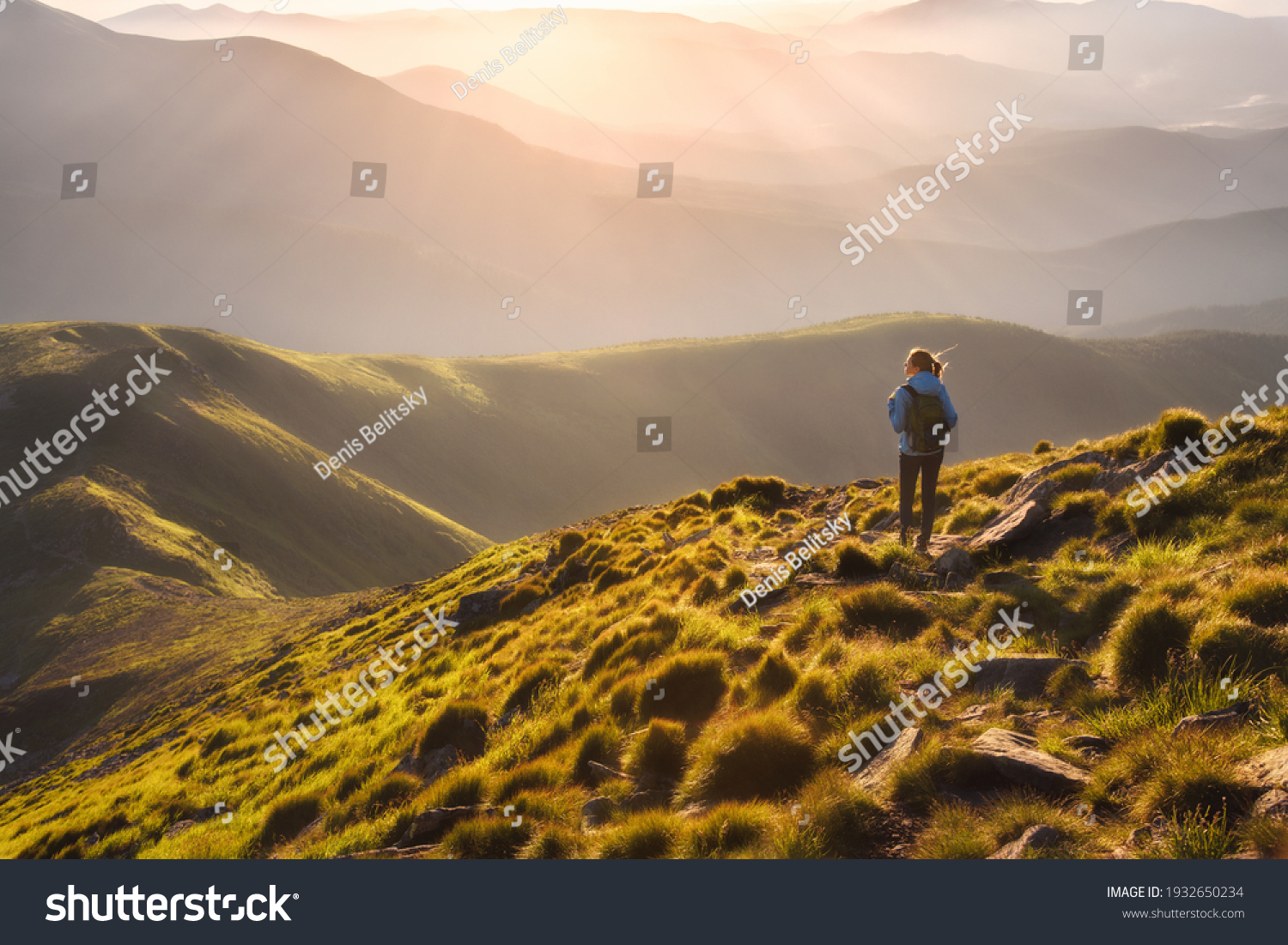 Girl on mountain peak with green grass looking at beautiful mountain valley in fog at sunset in summer. Landscape with young woman on the trail, foggy hills, forest, sky. Travel and tourism. Hiking #1932650234