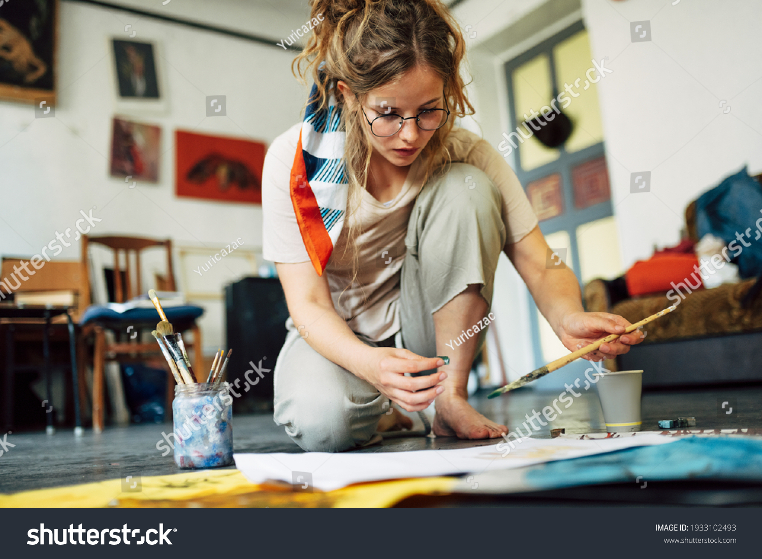 Horizontal image of a pretty female artist sitting on the floor in the art studio and painting on paper with a brush. A woman painter with glasses painting with watercolors in the workshop. #1933102493