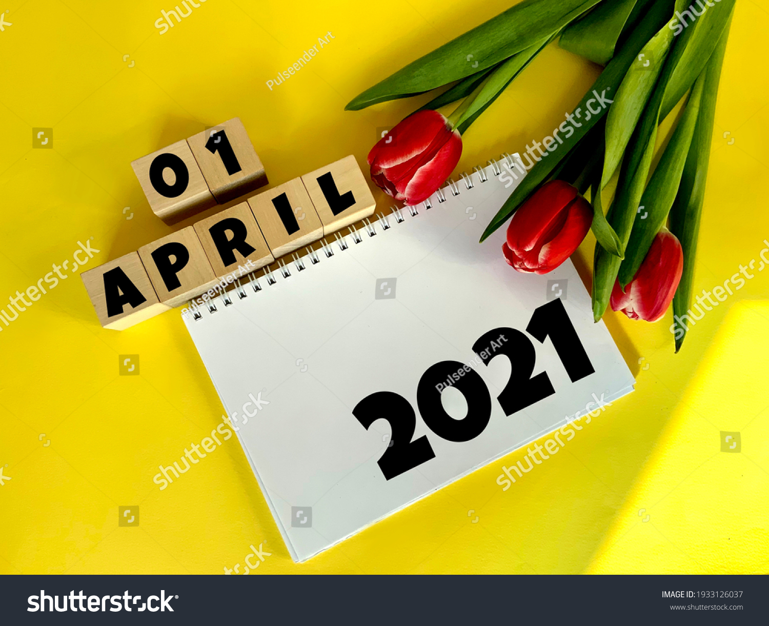 April 1 on wooden cubes.Next to it are tulips and a white notebook with the inscription 2021 on a yellow background.Calendar for April. #1933126037