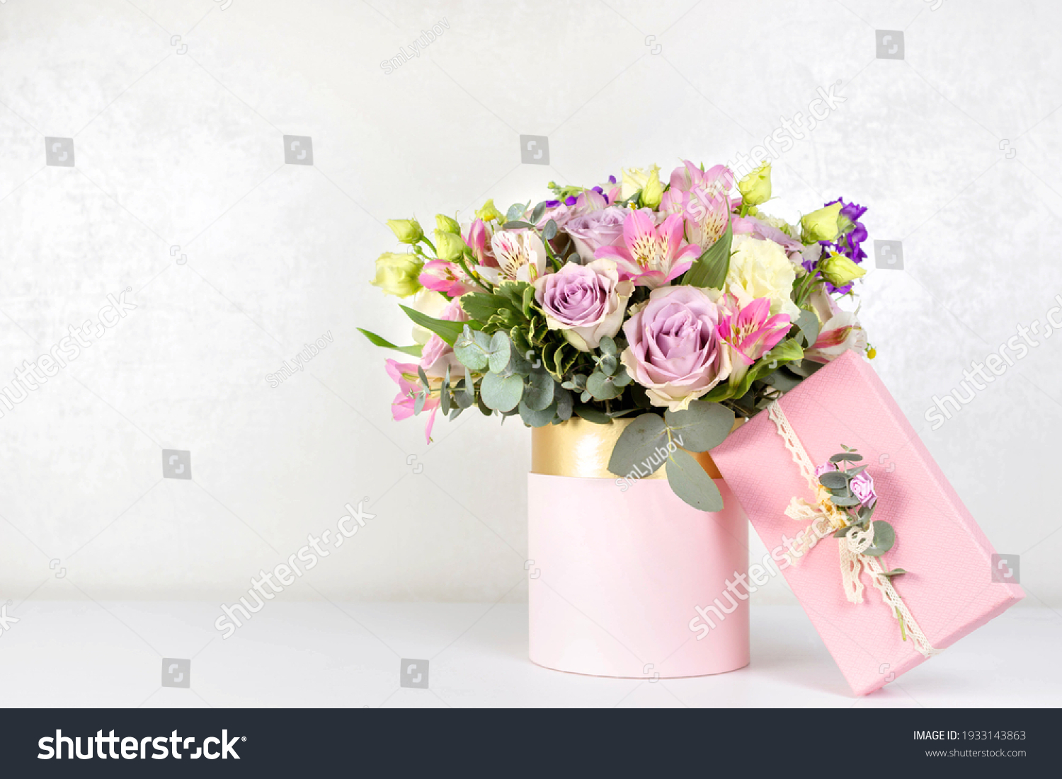 Beautiful bouquet of flowers in round box and pink gift box on a white table. Gift for holiday, birthday, Wedding, Mother's Day, Valentine's day, Women's Day. Floral arrangement in a hat box. #1933143863