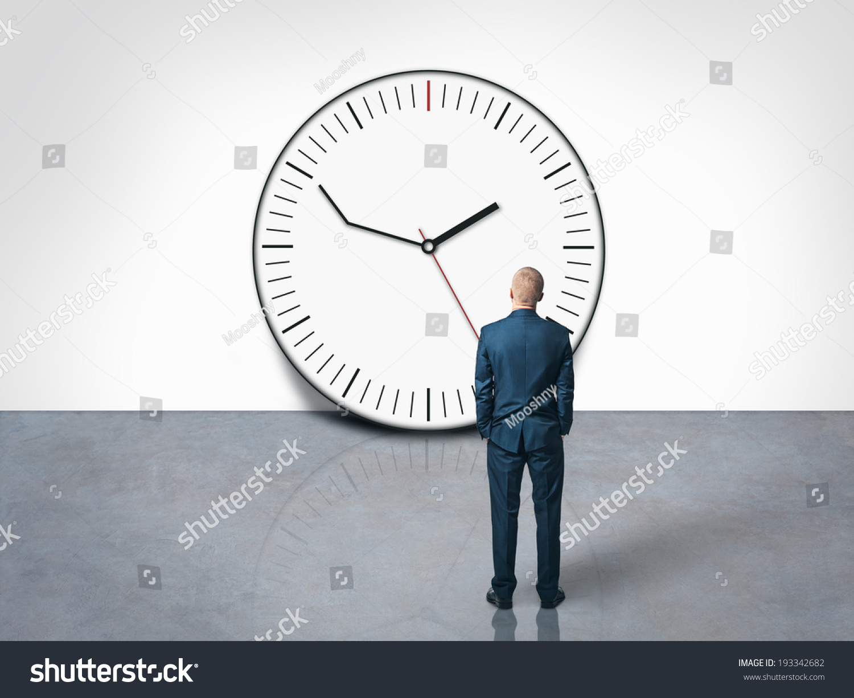 Man looking delay clock on wall stock photo 193342682 shutterstock man looking at the delay clock on the wall amipublicfo Gallery