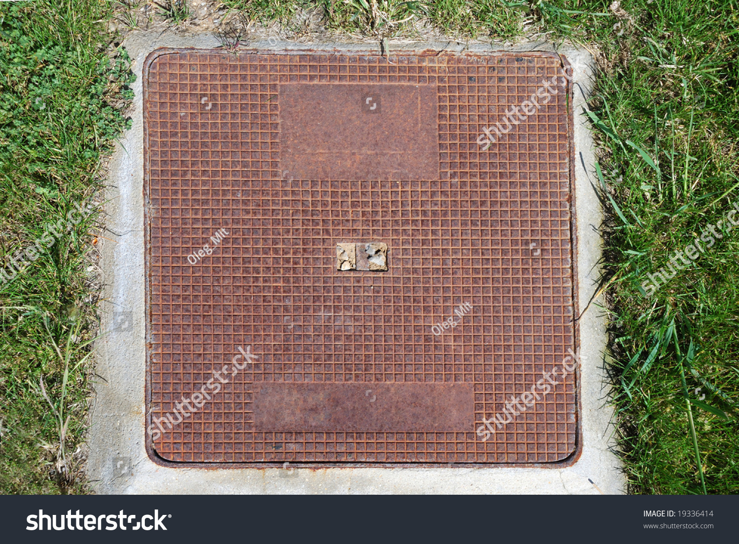 Square Metal Sewer Hatch With Light Rust On The Concrete