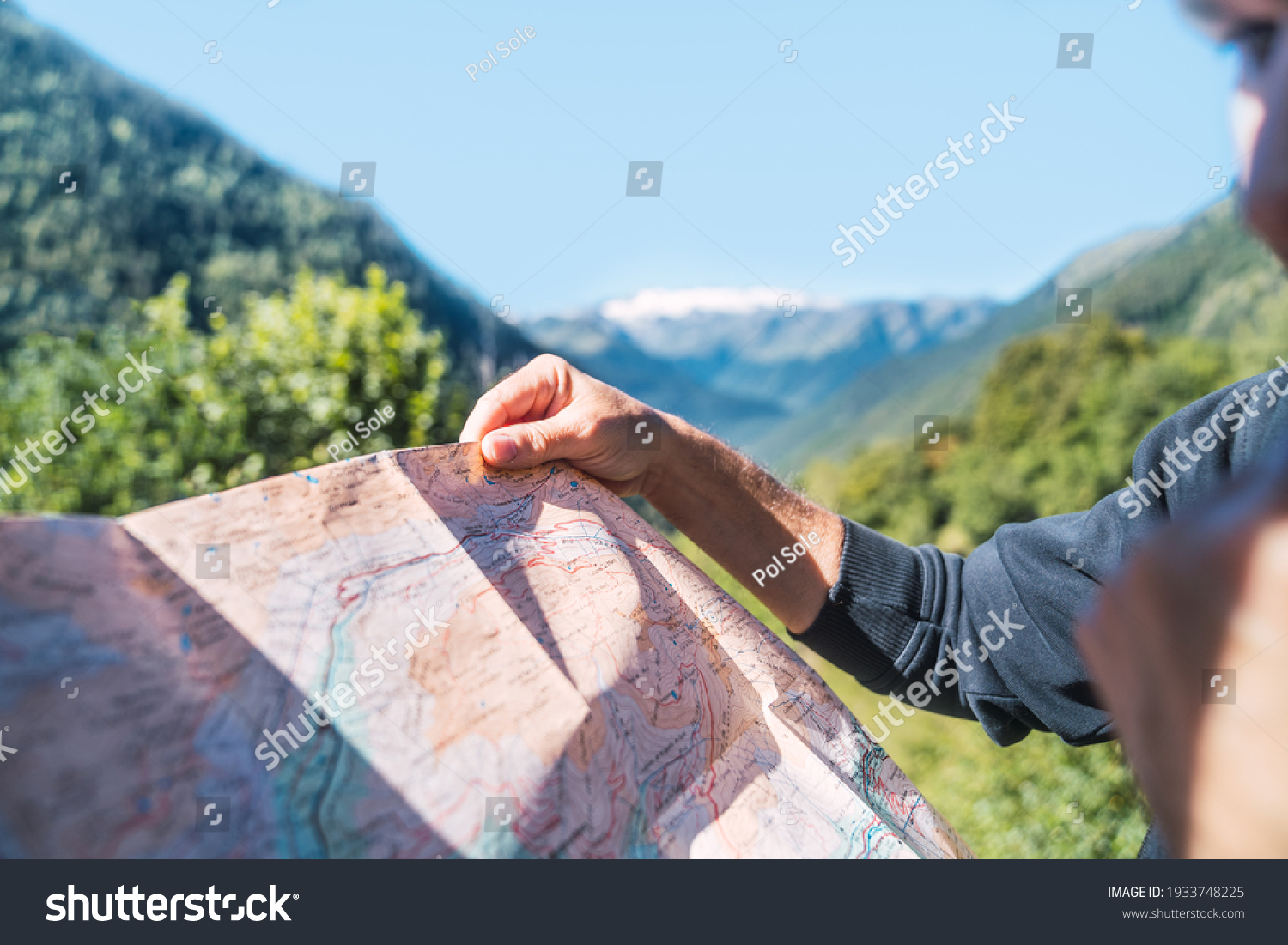 Anonymous man looking the travel route on a map in the mountain. Routes, excursions and mountain trails through nature in summer. Concept of exploring and live adventures traveling in nature. #1933748225