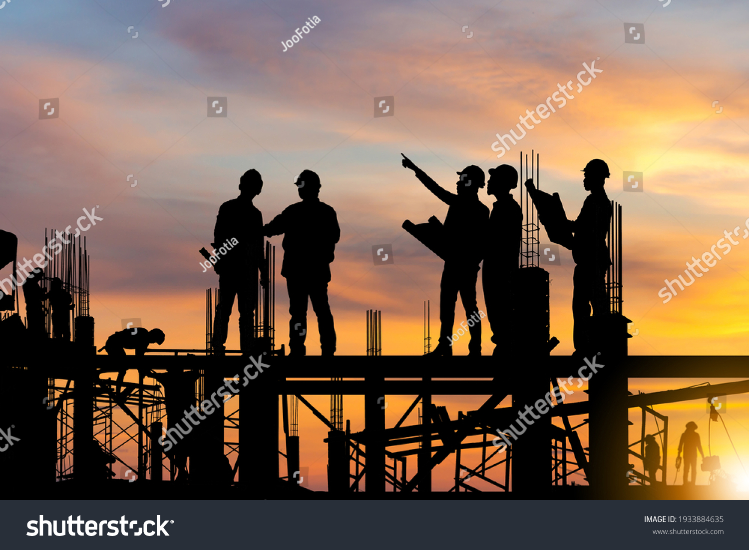 Silhouette of Engineer and worker on building site, construction site at sunset in evening time. #1933884635
