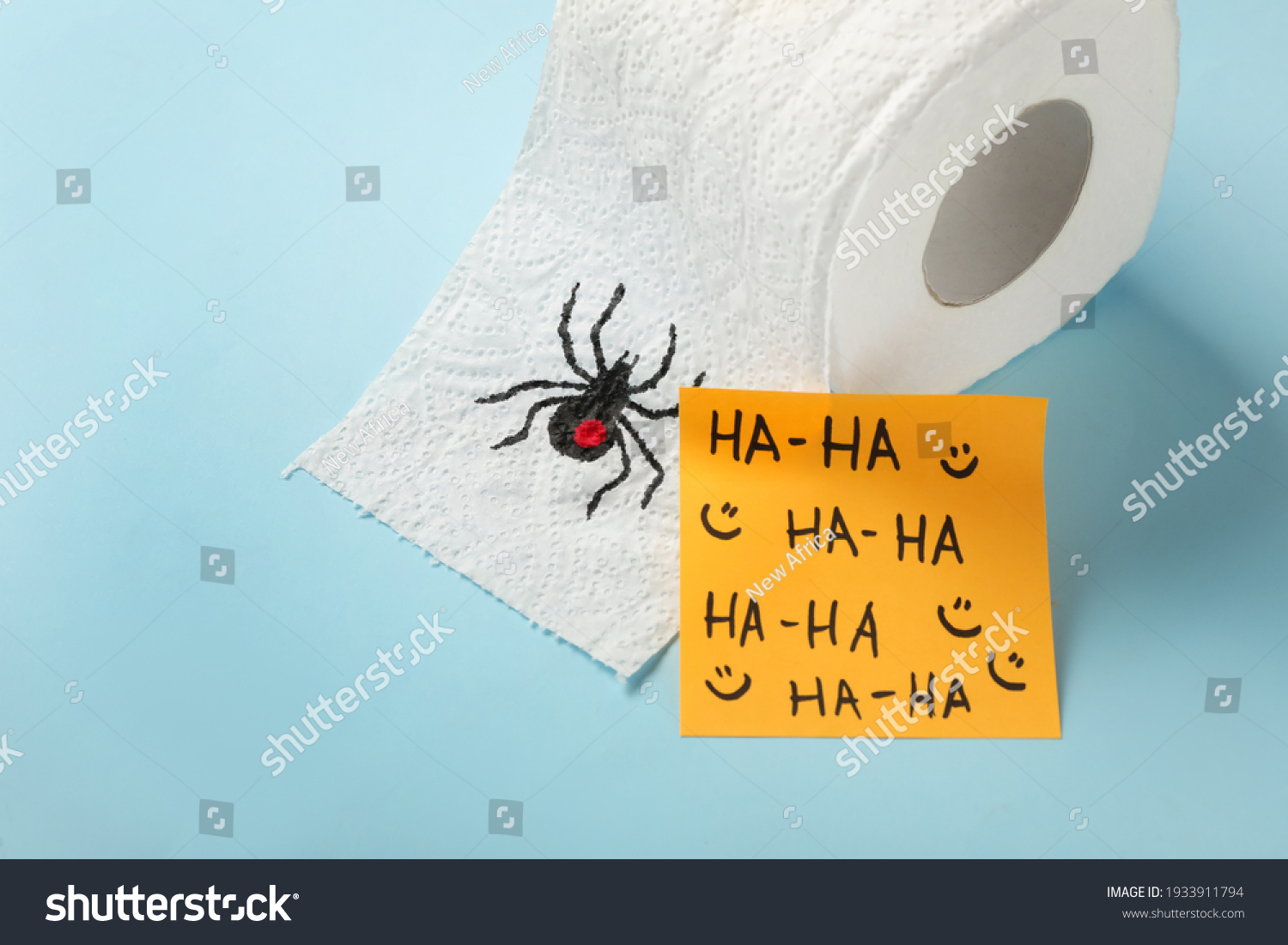 Toilet paper roll with drawn spider and words Ha-Ha  on light blue background. Celebrating April Fool's Day #1933911794