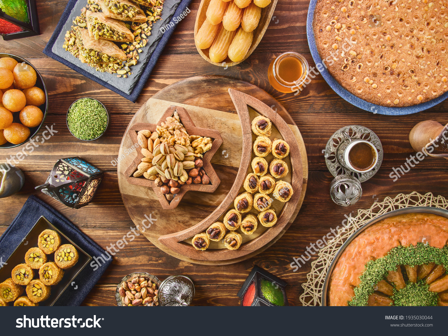 Arabic Cuisine: Middle Eastern desserts. Delicious collection of Ramadan traditional desserts. Served with tasty nuts, Arabic coffee, honey syrup and sugar syrup .Top view with close up. #1935030044