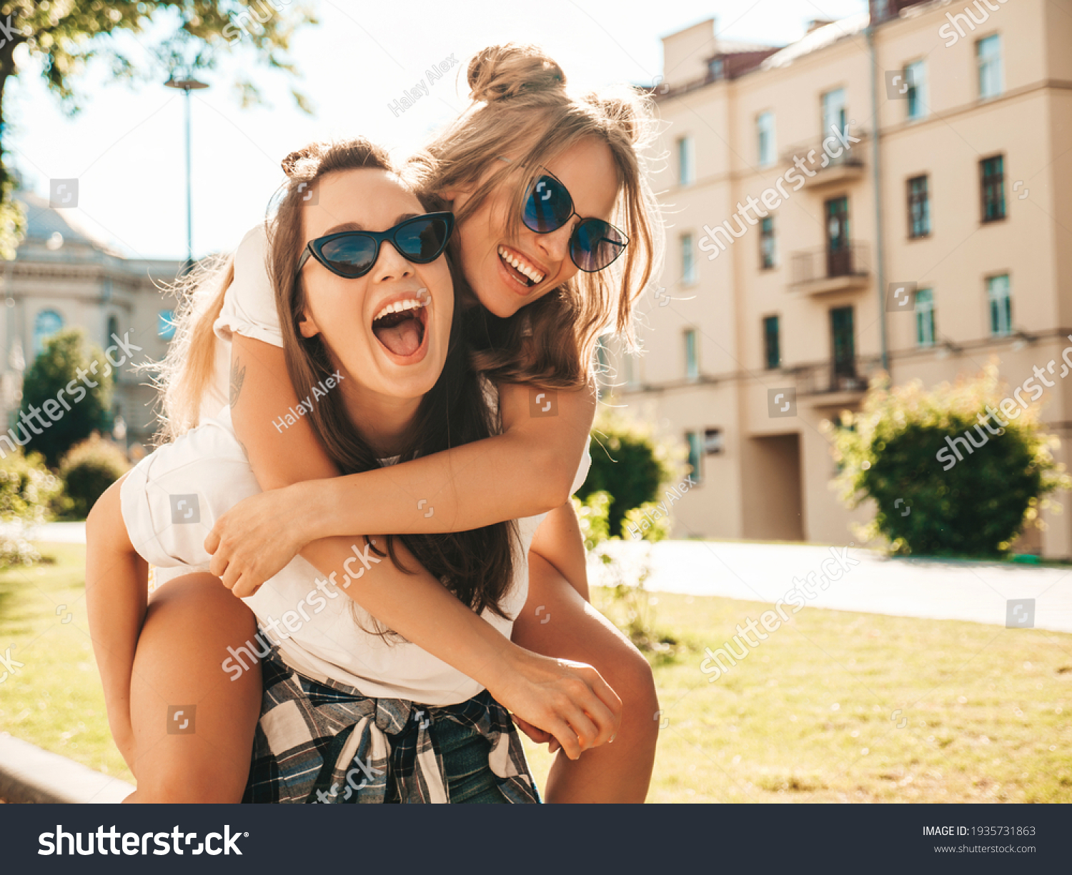 Two young beautiful smiling hipster female in trendy summer white t-shirt clothes.Sexy carefree women posing on street background. Model jumping on her friend back, gives piggyback riding outdoors #1935731863