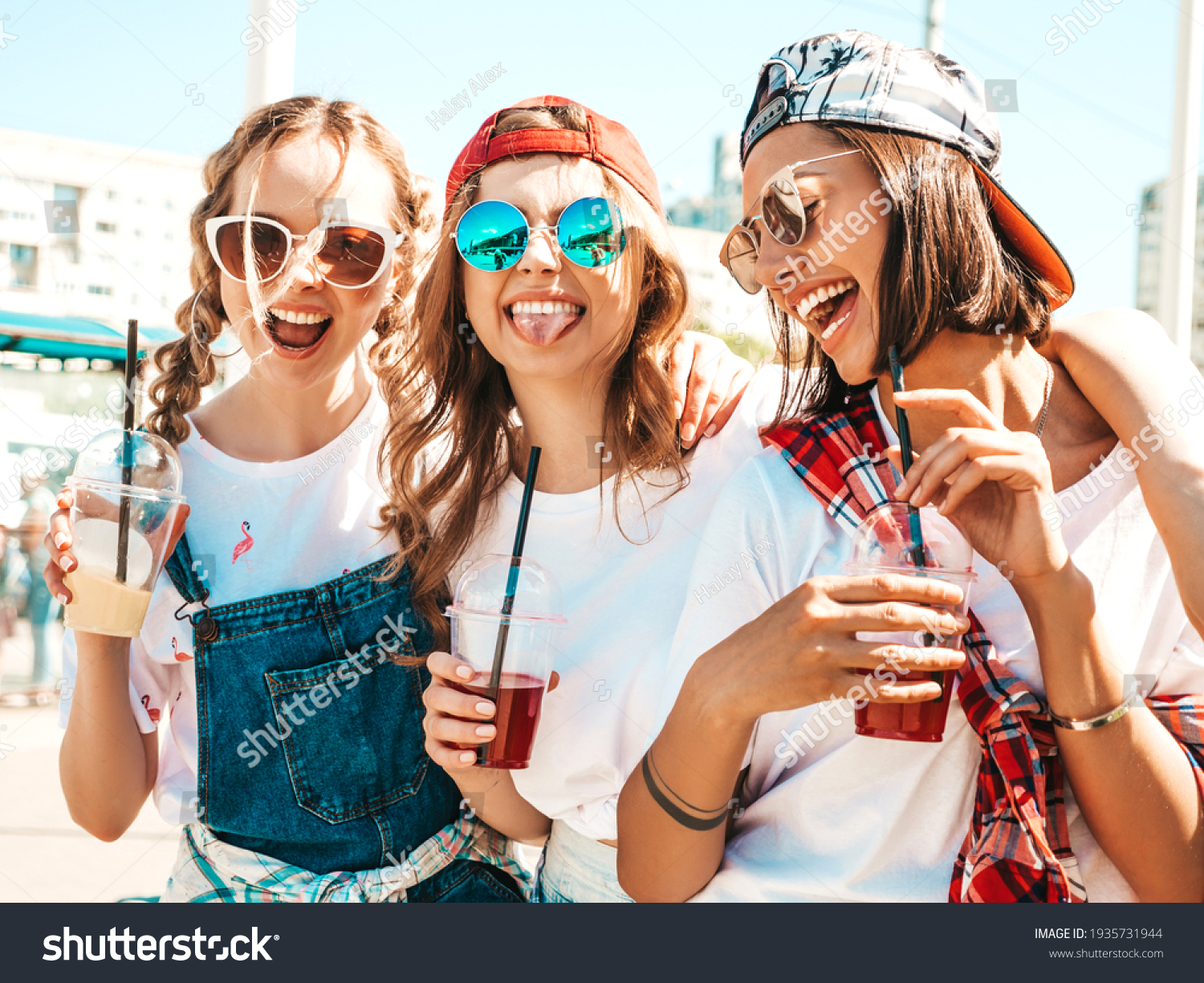 Three young beautiful smiling hipster female in trendy summer clothes.Sexy carefree women posing outdoors.Positive models holding and drinking fresh cocktail smoothie drink in plastic cup with straw #1935731944