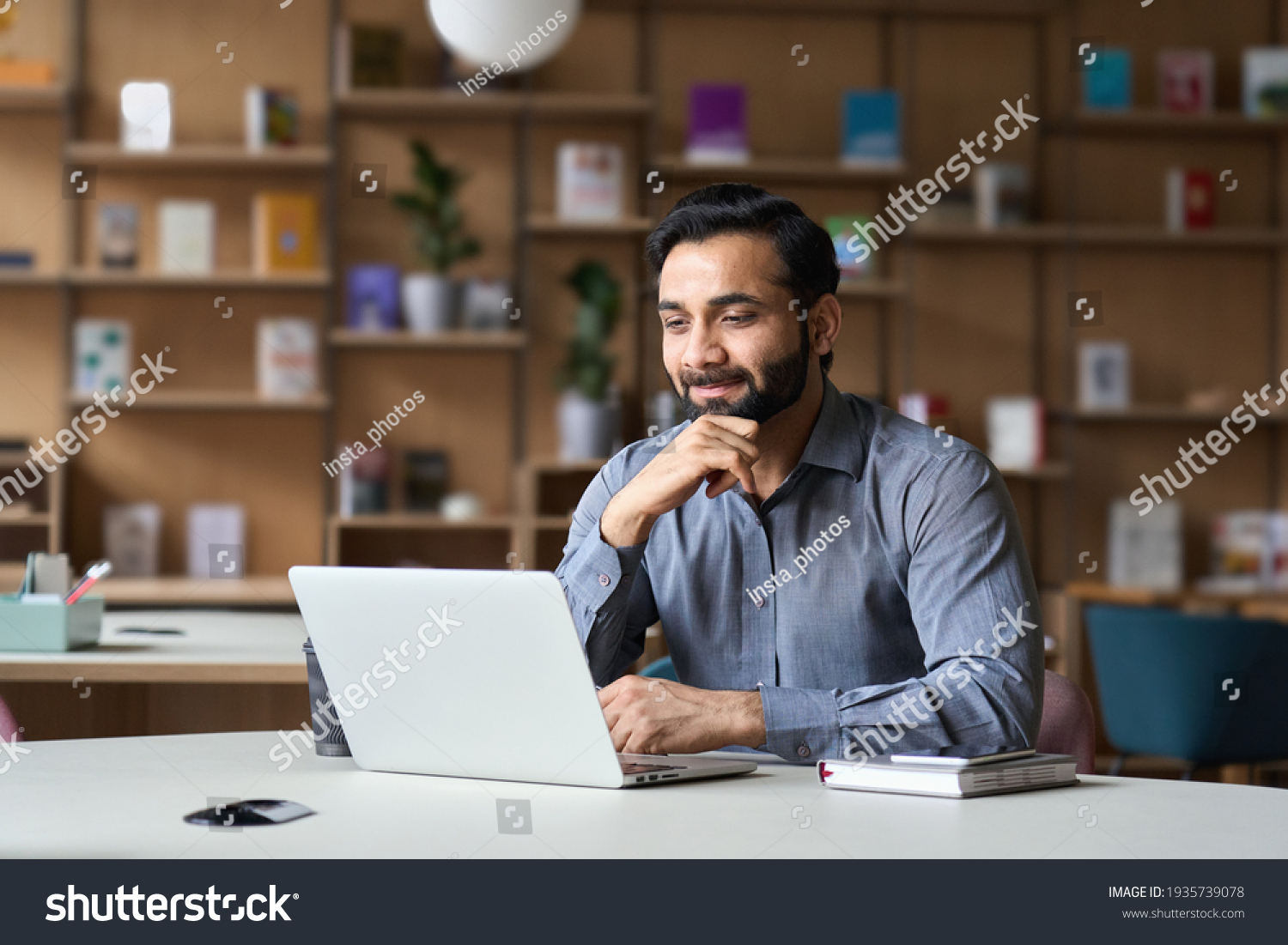 Smiling indian businessman working on laptop in modern office lobby space. Young indian student using computer remote studying, watching online webinar, zoom virtual training on video call meeting. #1935739078