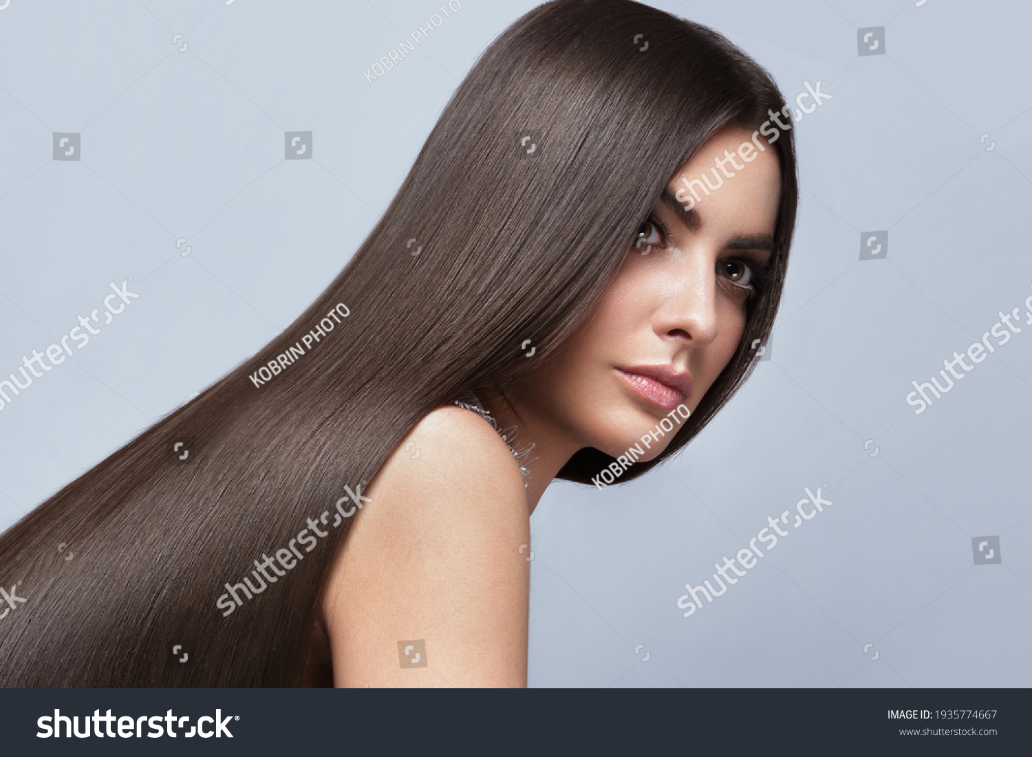 Beautiful brown-haired girl with a perfectly smooth hair, and classic make-up. Beauty face and hair. #1935774667