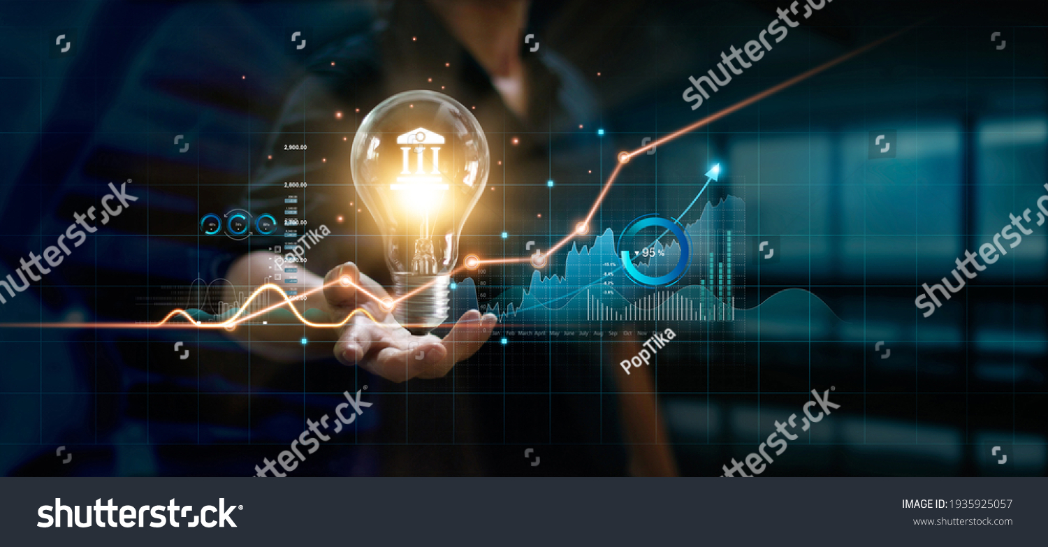 Businessman holding creative light bulb with growth graph and banking icons. Financial innovation technology develop new products and services that enhance successful and profit in global business. #1935925057
