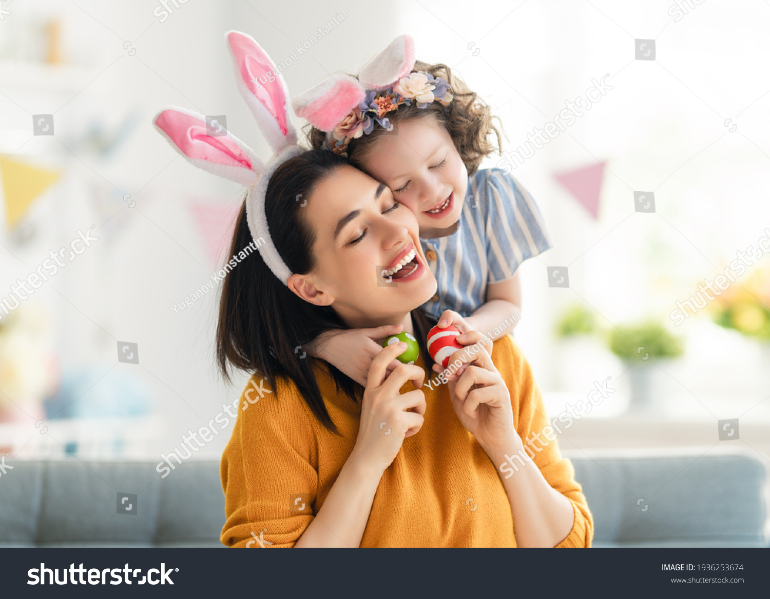 Happy holiday! Mother and her daughter with painting eggs. Family celebrating Easter. Cute little child girl is wearing bunny ears.  #1936253674